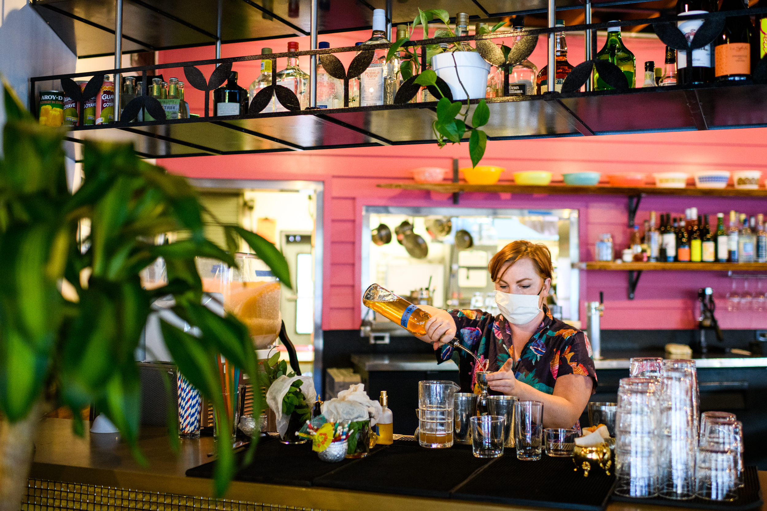 Oma's Hideaway bartender Emily Warden wears a mask while pouring a shot in a shaker in Portland, Oregon.