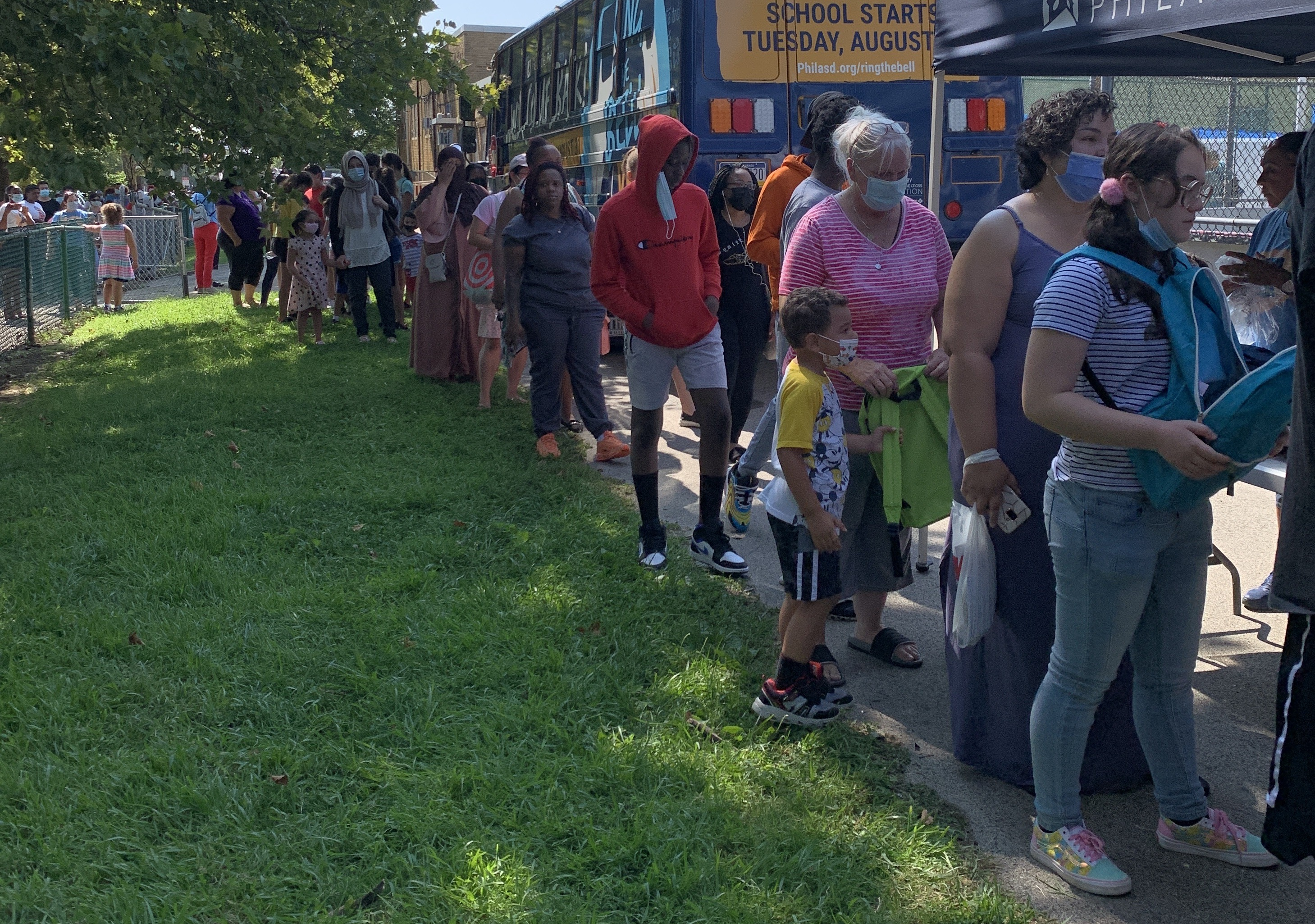 A long line of families wait near Cottman Avenue in the Northeast. They stand on a sidewalk next to a grassy area.