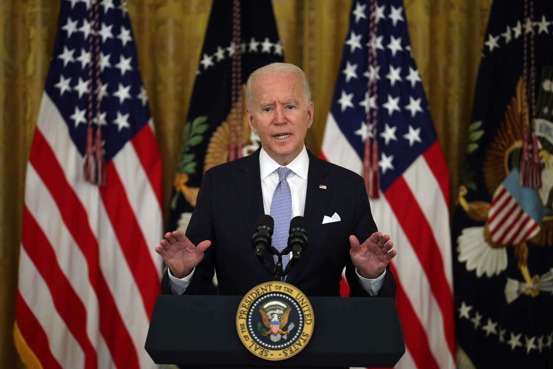 Joe Biden standing at a lectern bearing the presidential seal, before a background of U.S. flags