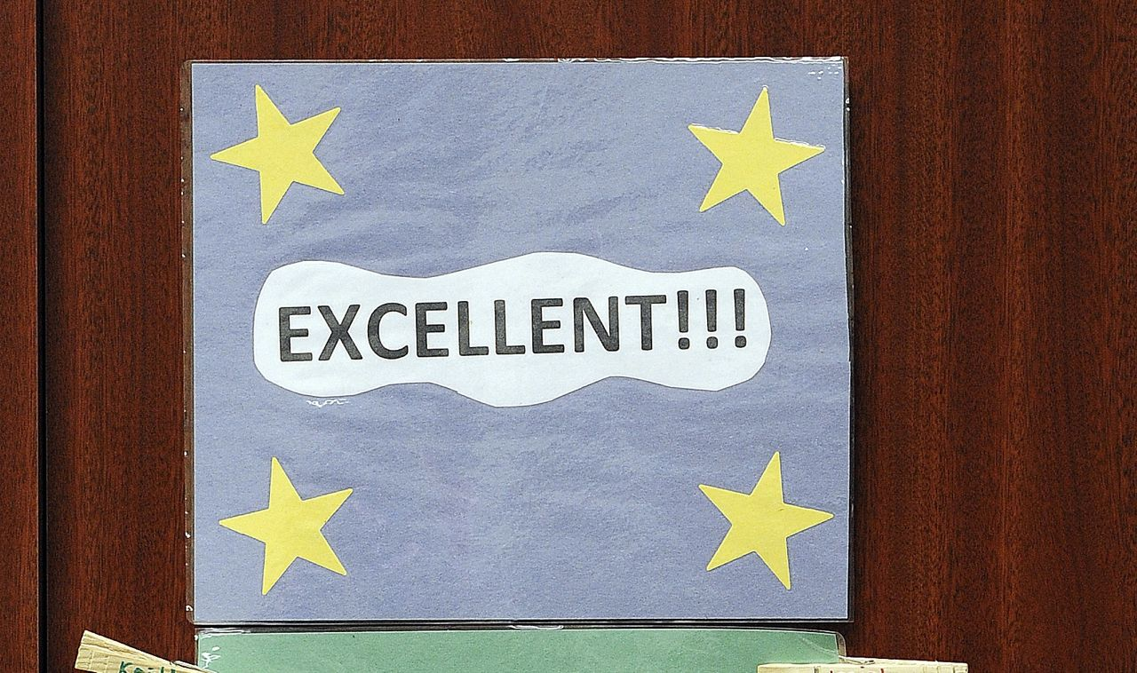 """A pale blue poster proclaiming """"Excellent!!!"""" with four yellow stars in the corners hangs on a wall."""