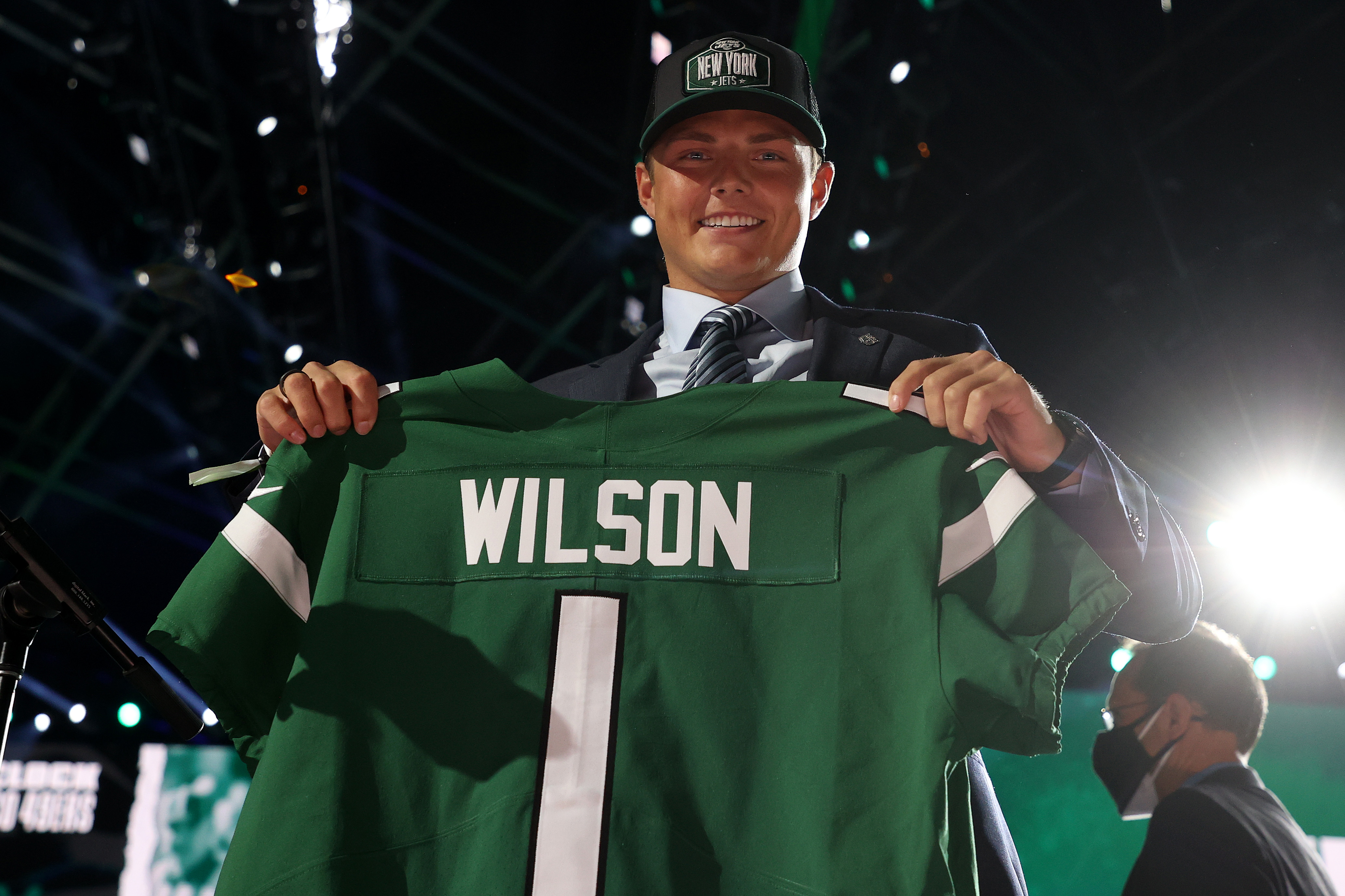 Zach Wilson holds a jersey onstage after being drafted second by the New York Jets during round one of the 2021 NFL Draft at the Great Lakes Science Center on April 29, 2021 in Cleveland, Ohio.