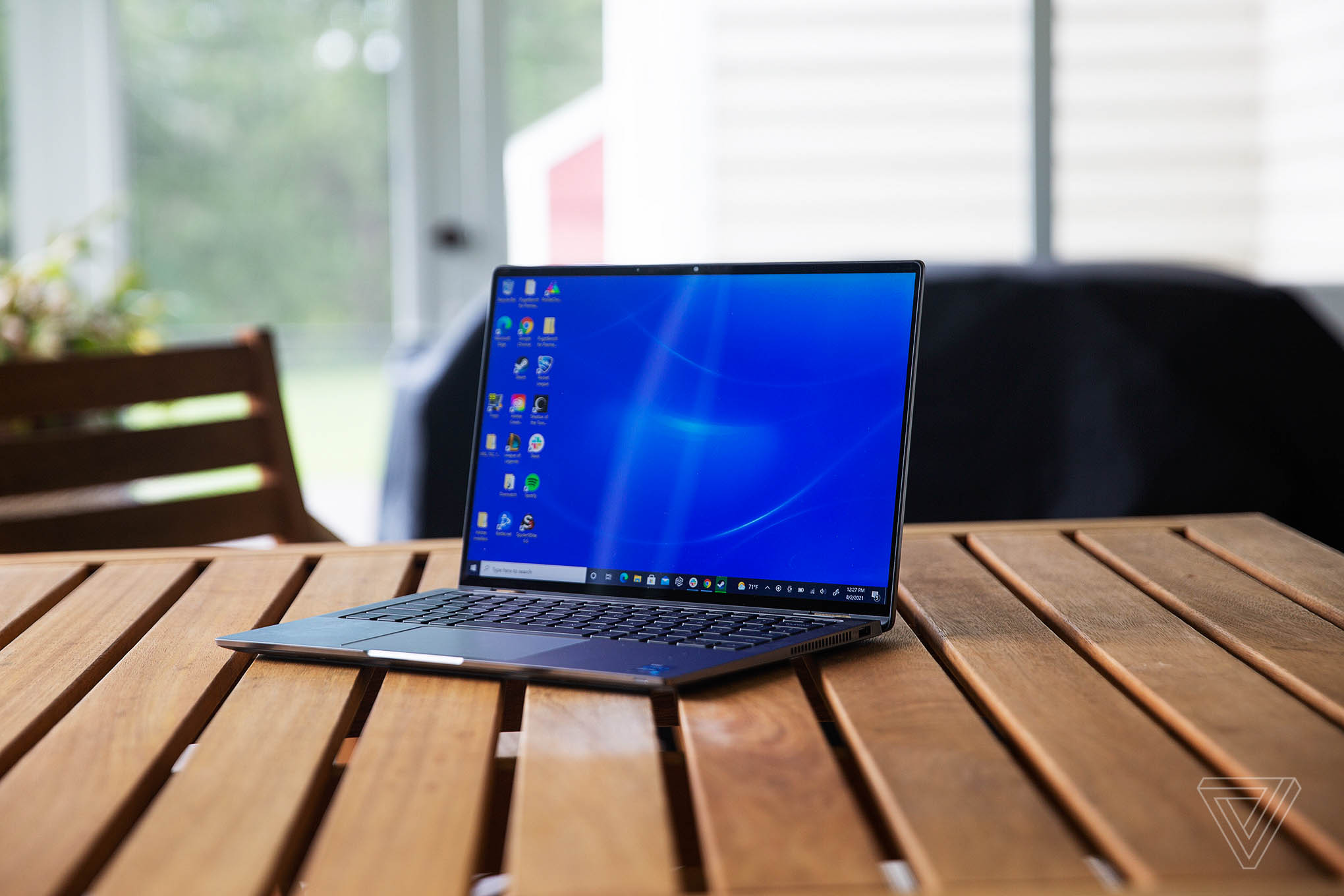 The Dell Latitude 9420 sits on a porch gable, facing to the left. The screen displays a desktop with a blue background.