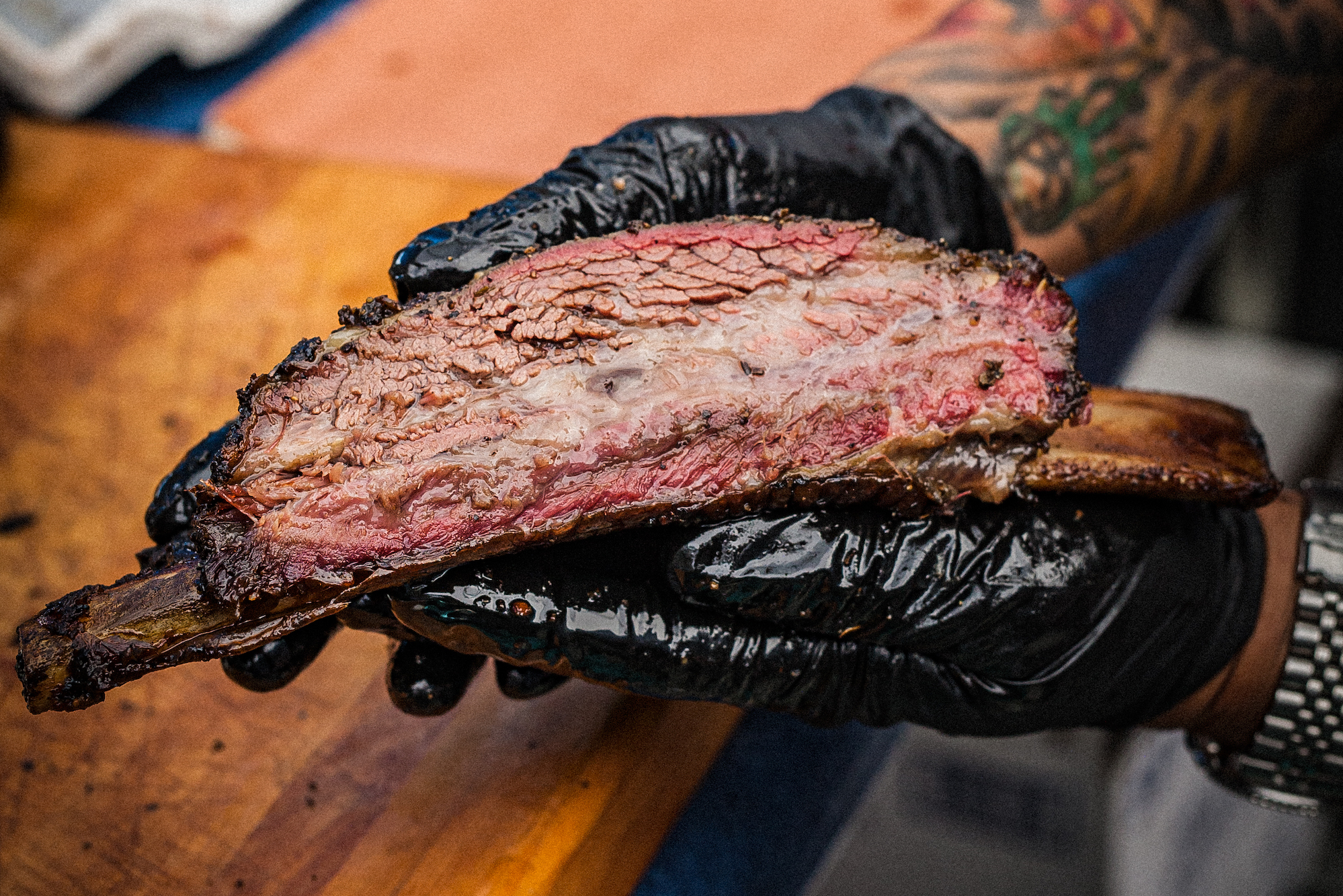 A beef rib fresh off the smoker held by black-gloved hands.