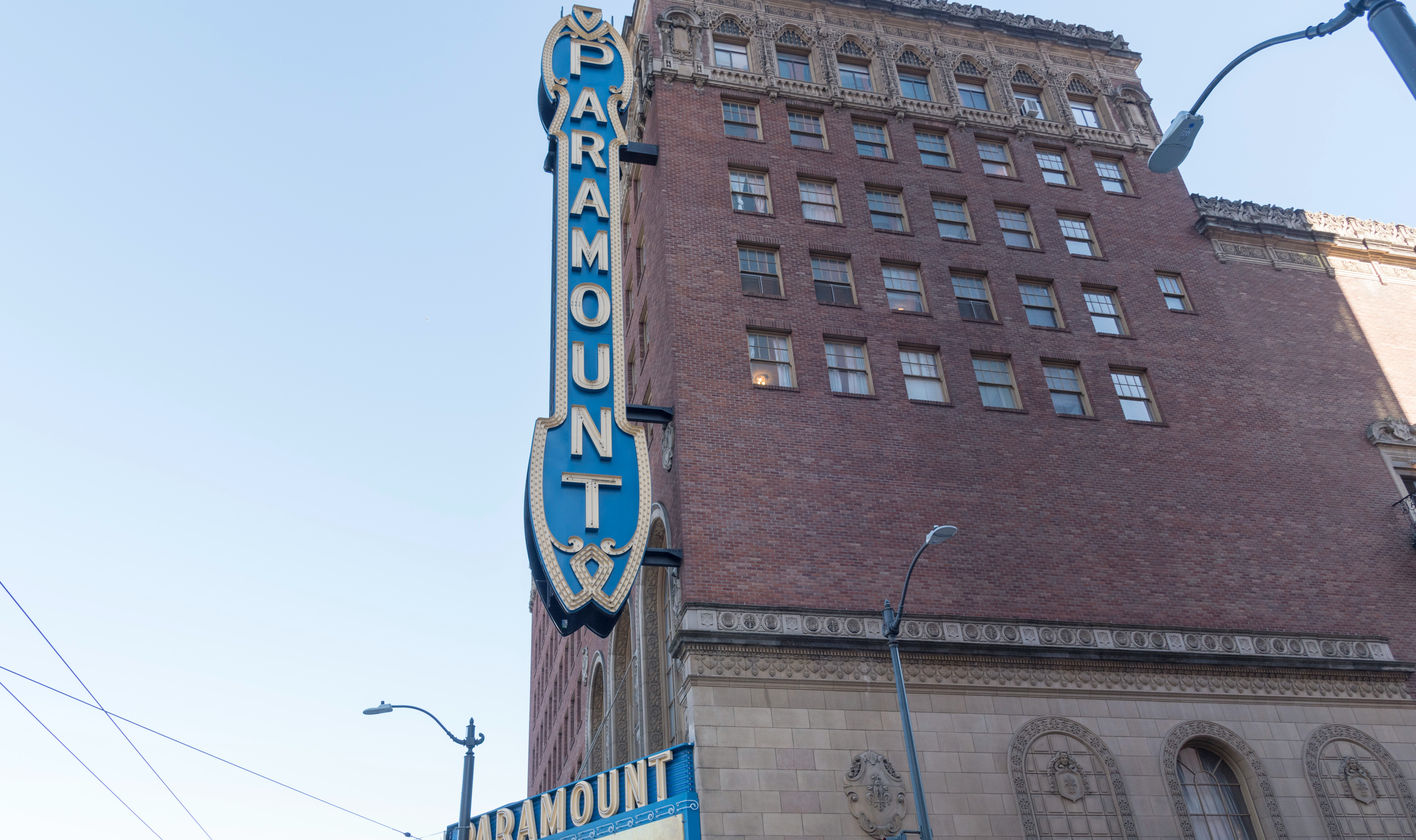 The exterior of the Paramount Theater in Seattle on a sunny day with the venue's name in a vertical sign on the brick facade.