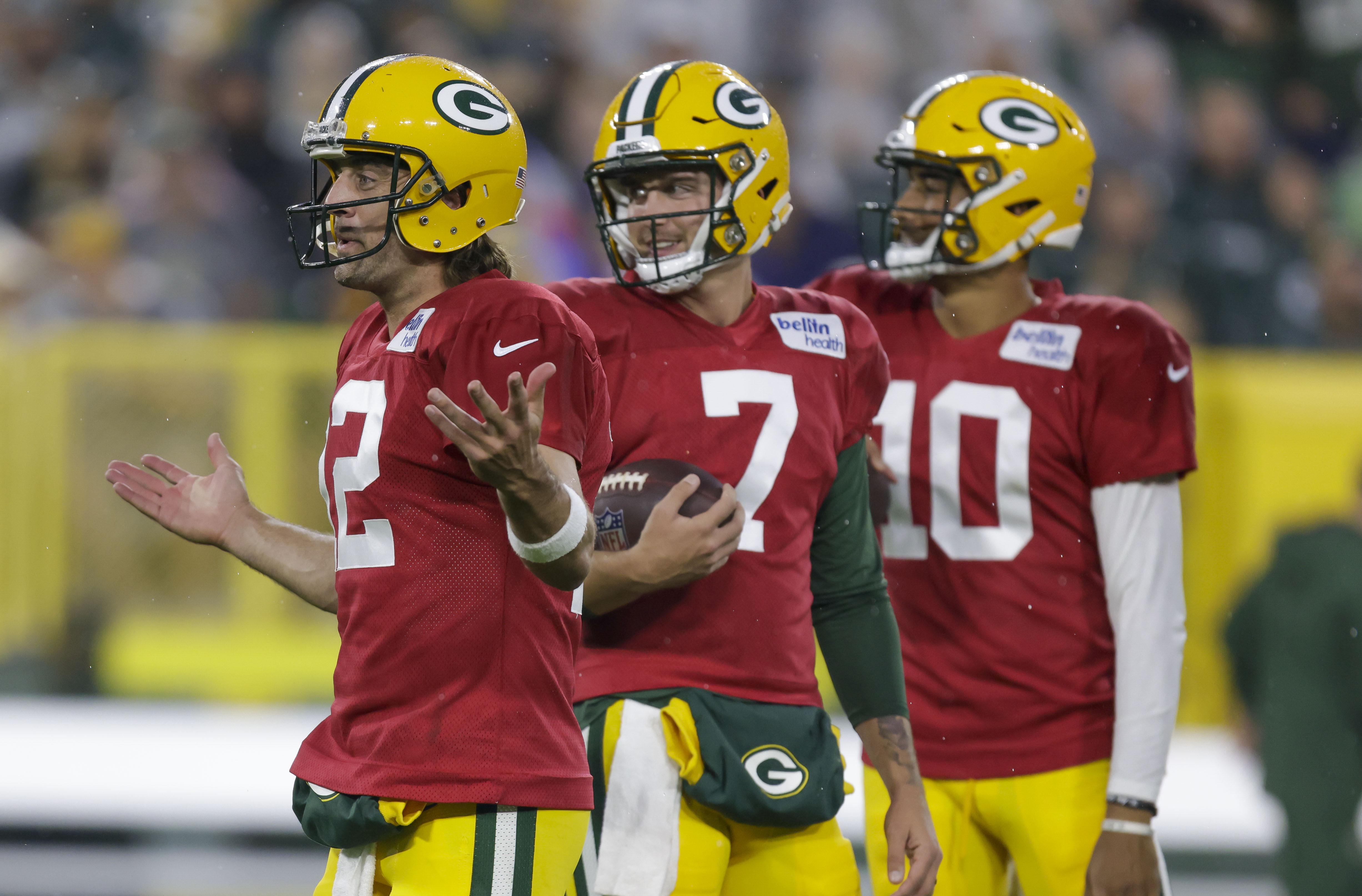 Green Bay Packers quarterback Aaron Rodgers (12) gestures to teammates while quarterbacks Kurt Benkert (7) and Jordan Love (10) look on.
