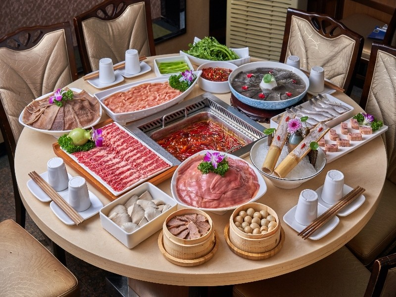 A table full of uncooked hot pot ingredients and a pot of broth.