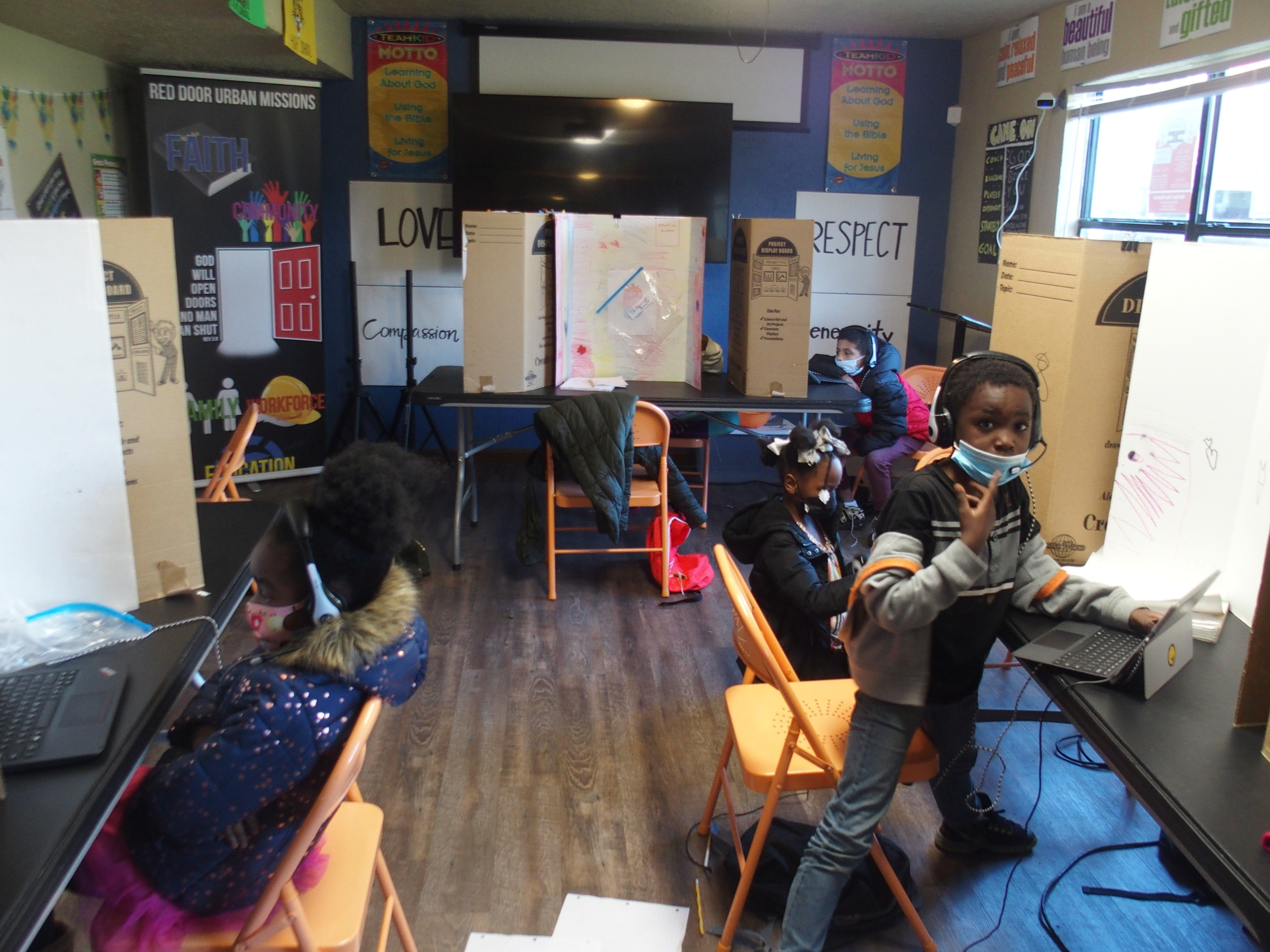 """Four children wearing masks and headphones work at laptop computers in a narrow classroom with orange folding chairs. Three hand-lettered posters on the walls read """"Respect,"""" """"Love,"""" and """"Compassion."""""""