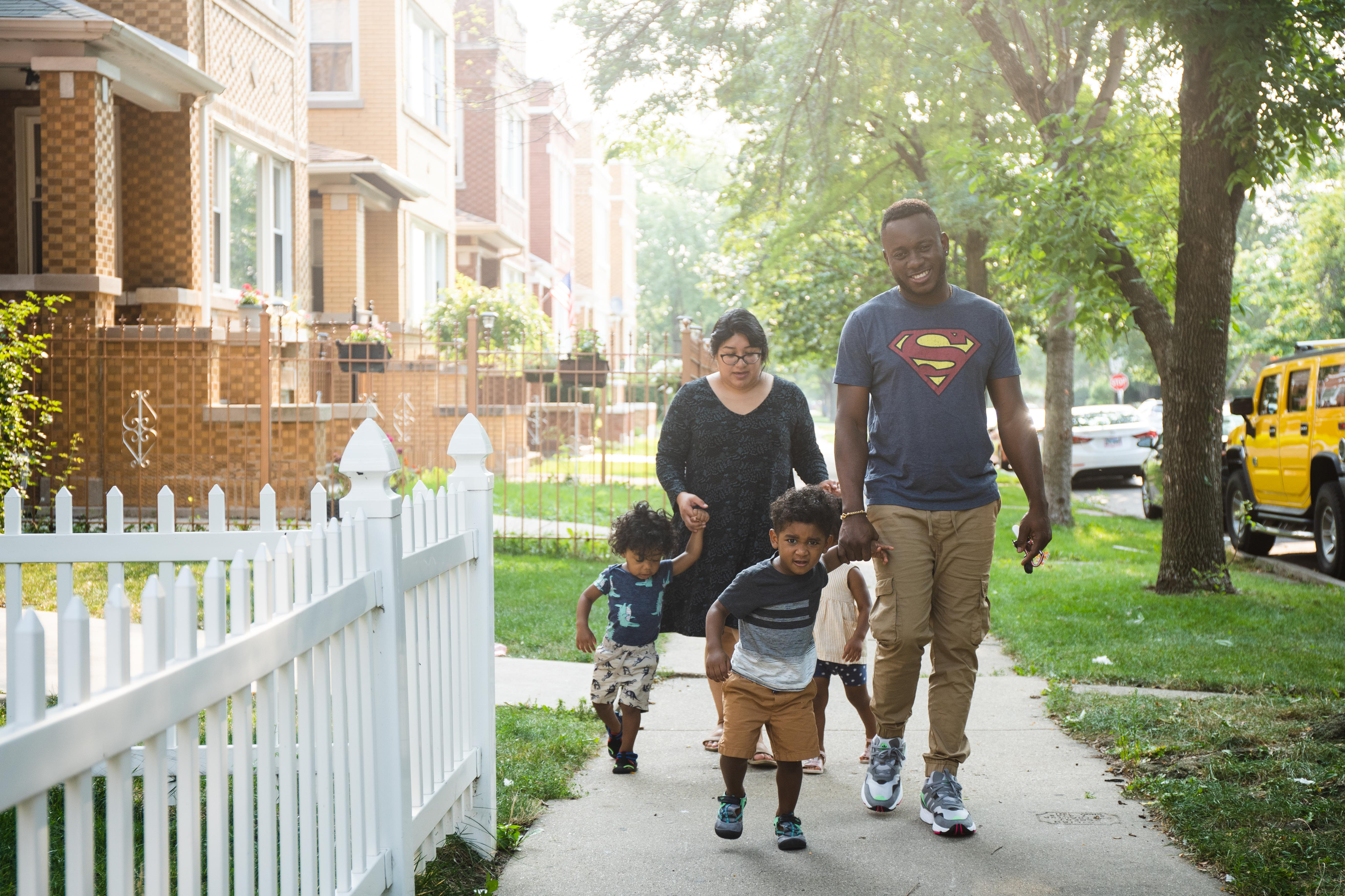 Maritza Bandera and her partner Roberto Parra walk to their car with their kids Gabriel Parra, front, and Eliel, back, outside their home in the Belmont Cragin neighborhood.