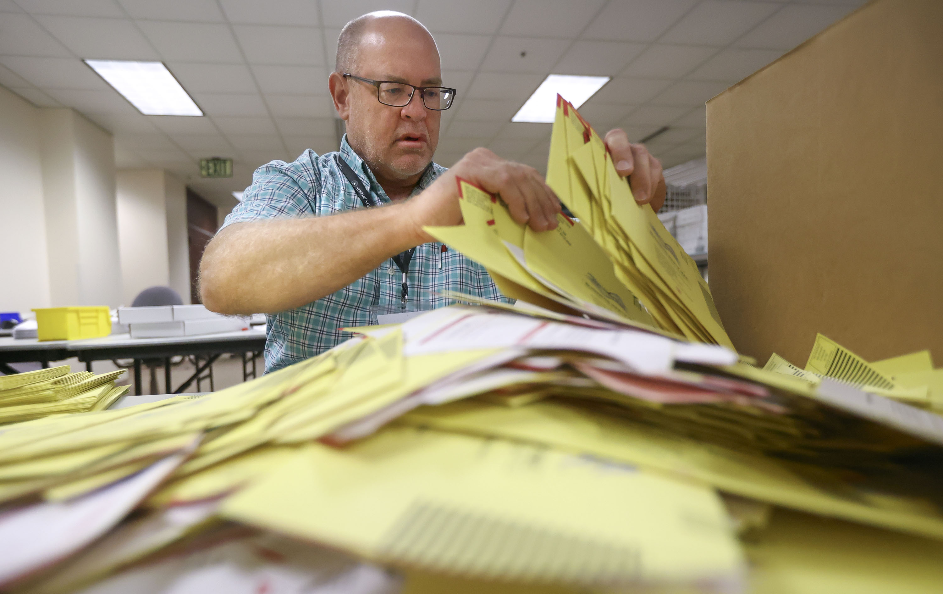 Elections coordinator Michael Fife gathers election envelopes at the Salt Lake County Government Center in Salt Lake City on Tuesday, Aug. 10, 2021.