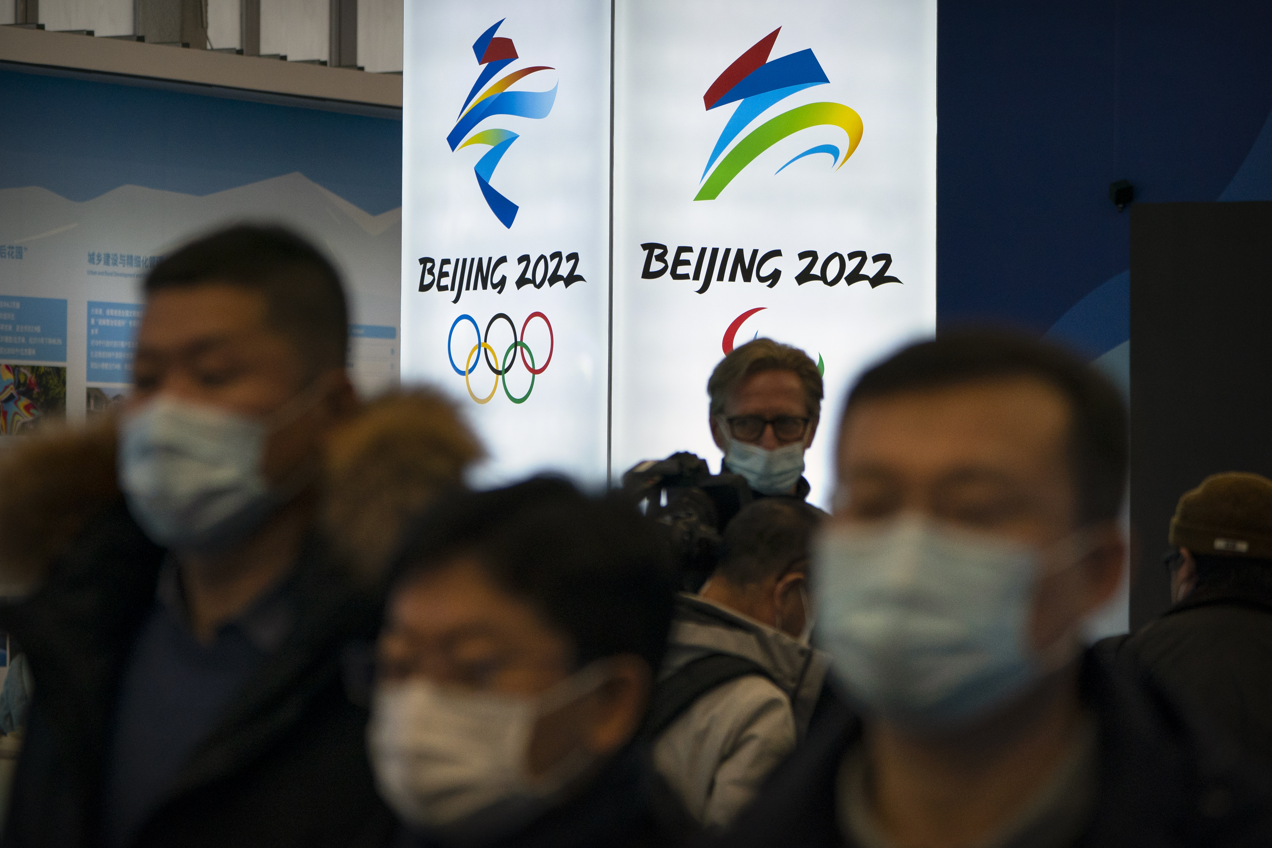 People wearing face masks to protect against the spread of COVID-19 look at an exhibit tied to the 2022 Olympic Winter Games.