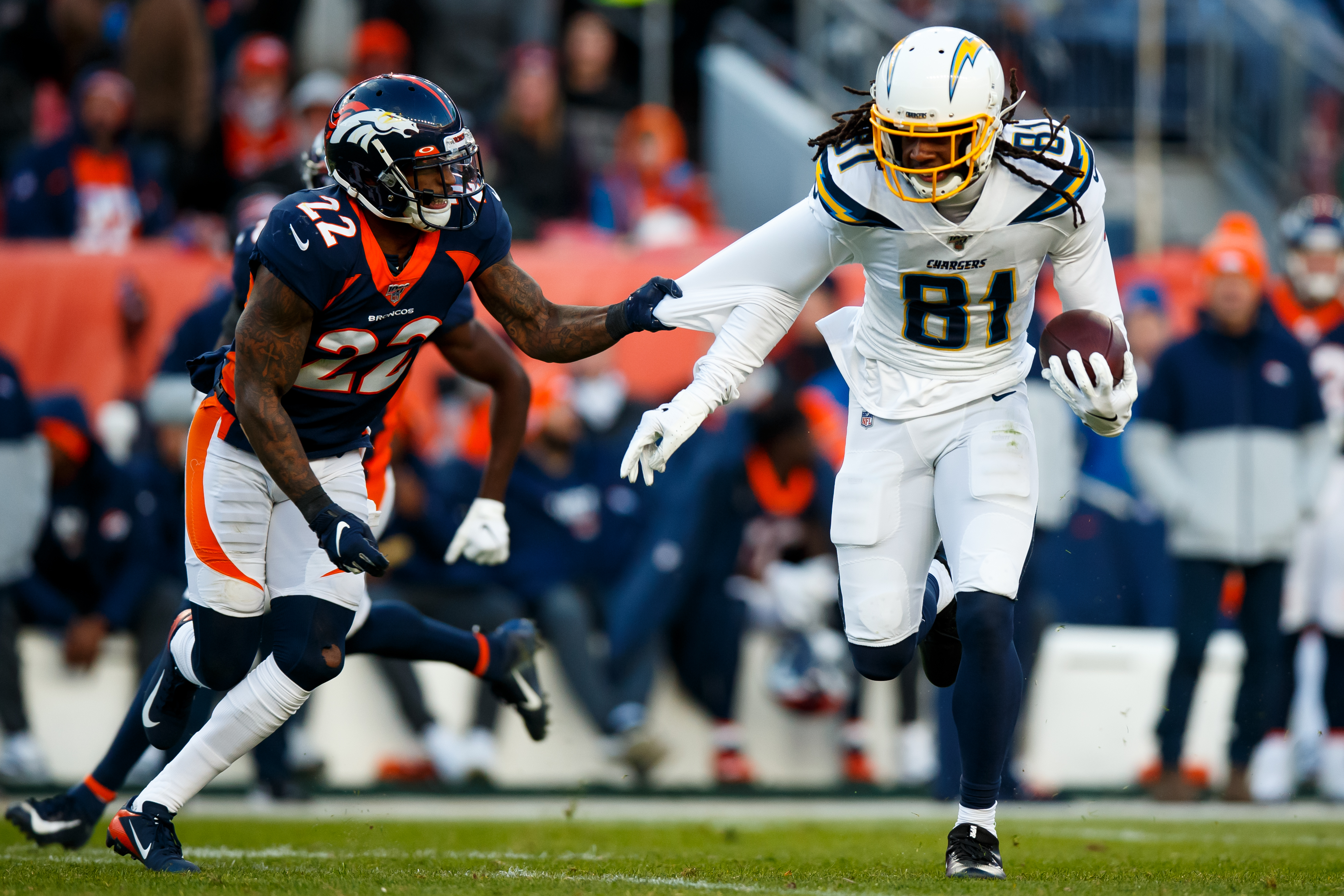 Wide receiver Mike Williams #81 of the Los Angeles Chargers tries to elude cornerback Kareem Jackson #22 of the Denver Broncos after catching a pass during the second quarter at Empower Field at Mile High on December 1, 2019 in Denver, Colorado.