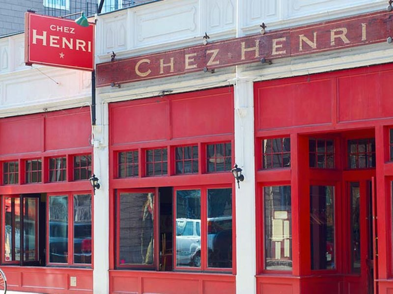 """A bright red restaurant exterior has red signage with gold lettering reading """"Chez Henri"""""""