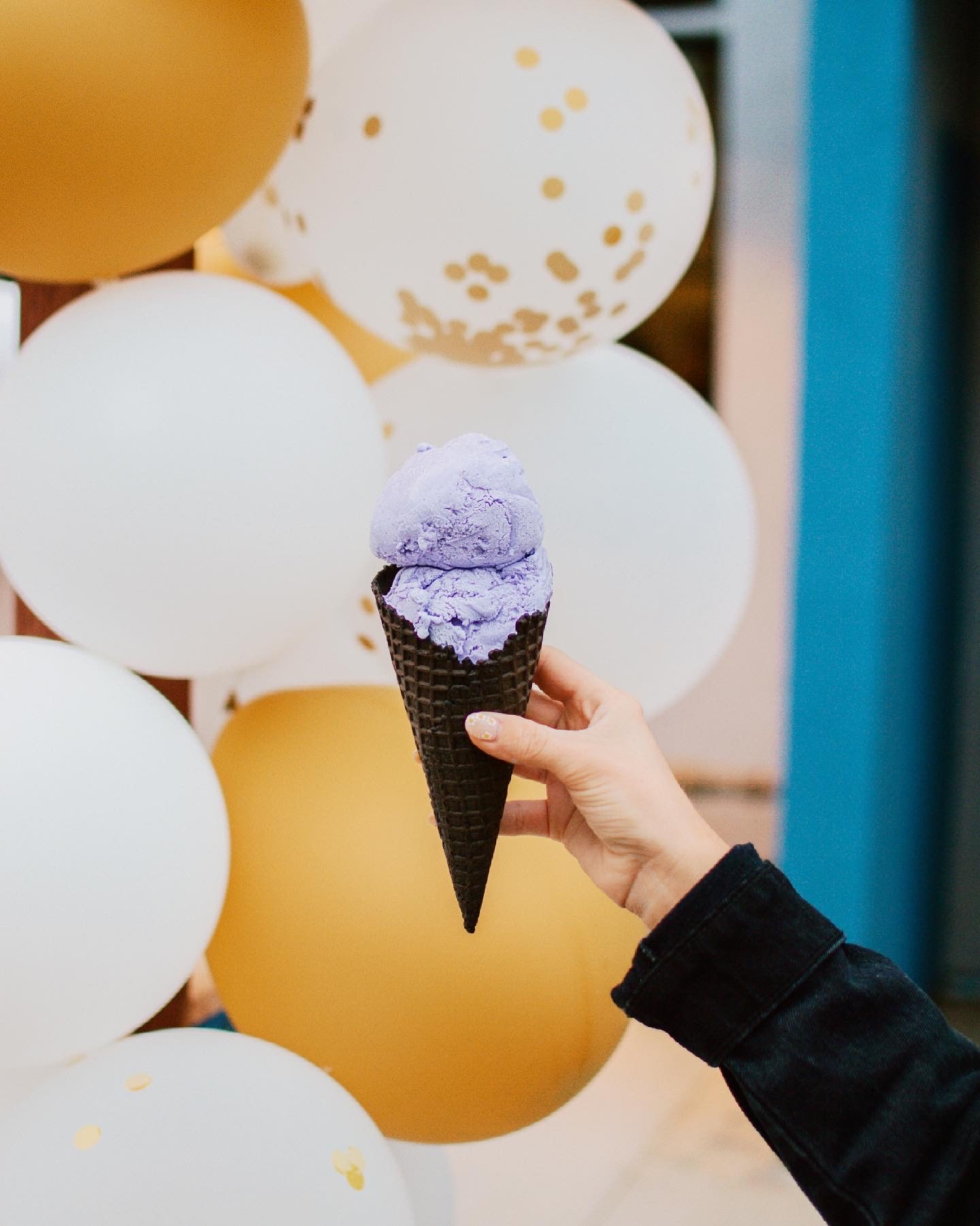 A hand holding a scoop of ice cream in front of balloons