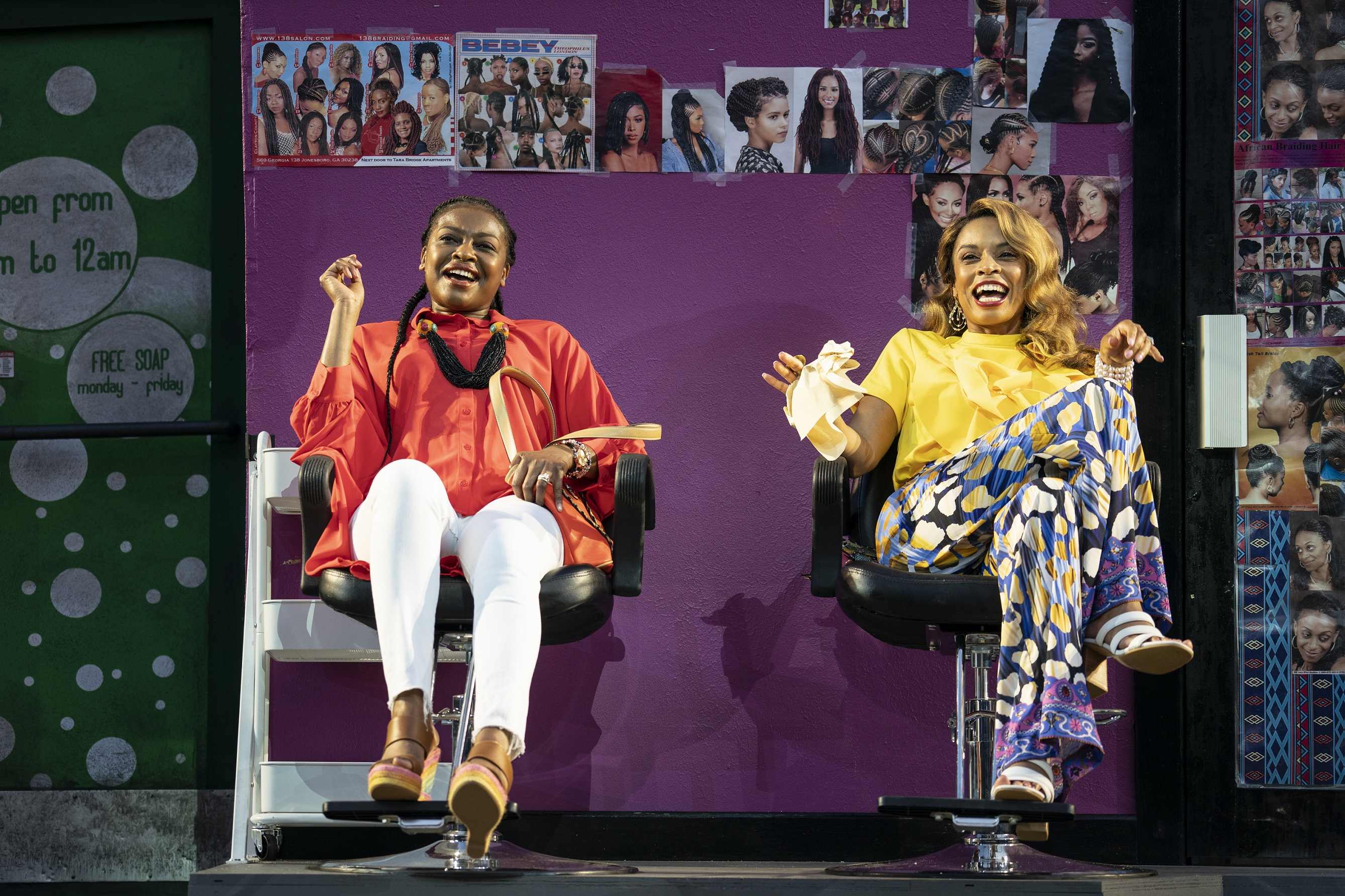 Two Black women sit, laughing, on a stage decorated to look like a beauty salon.