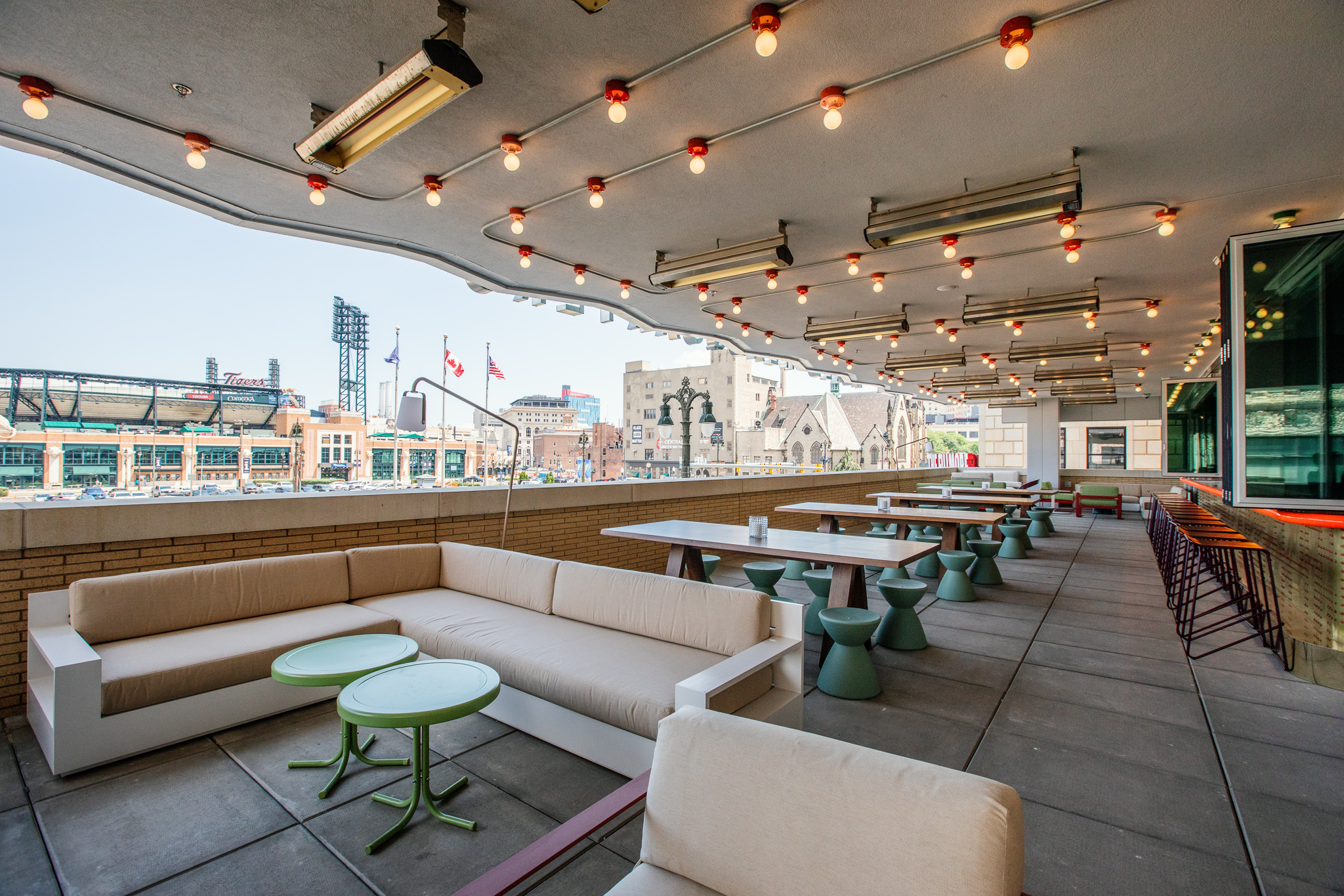 A patio with an indoor-outdoor bar and varied sofa and table seating looks out onto Woodward and Comerica Park