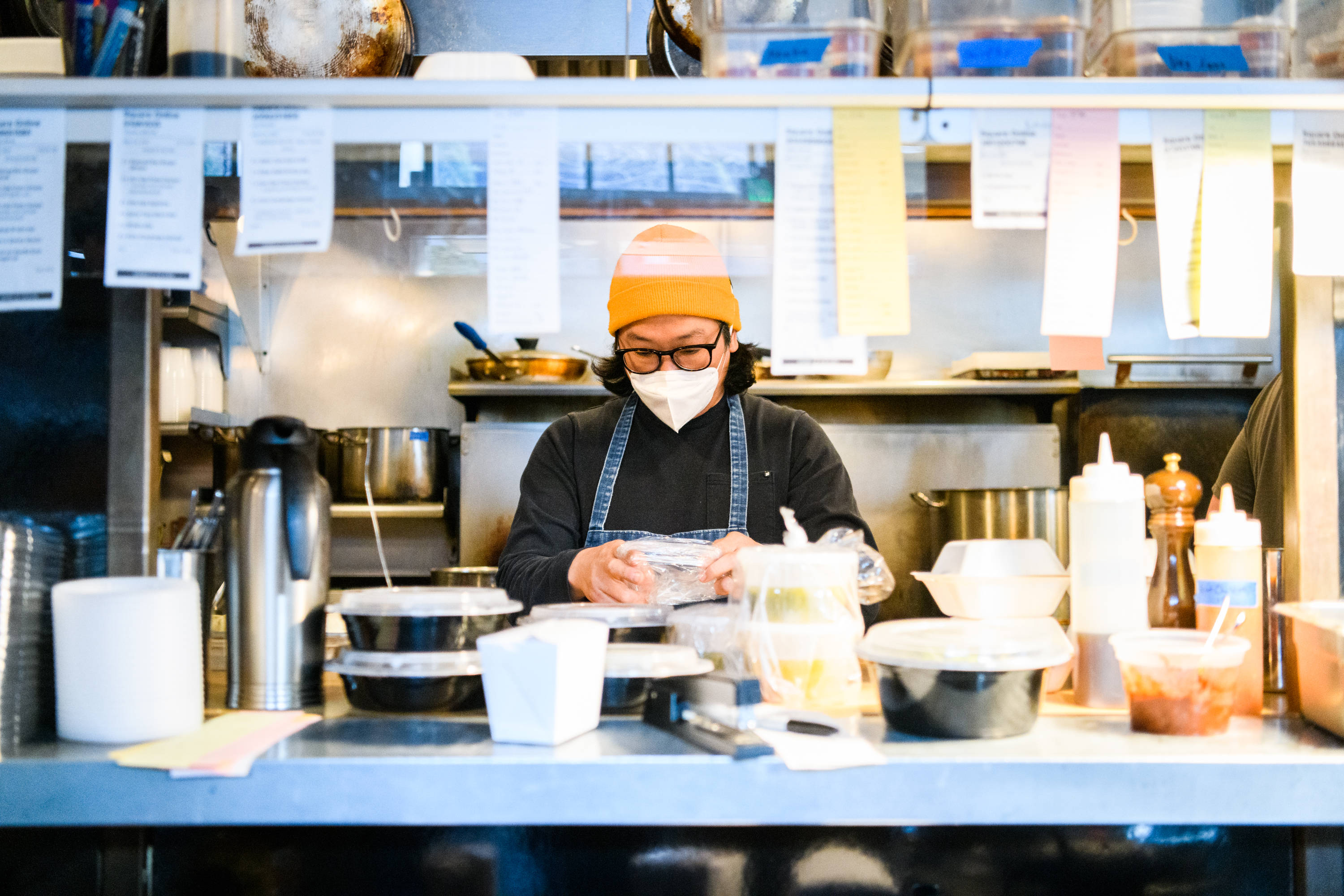 Peter Cho, the owner of restaurants Toki and Han Oak, wears a mask behind the pass in the kitchen of Toki, a Korean restaurant in Portland, Oregon.