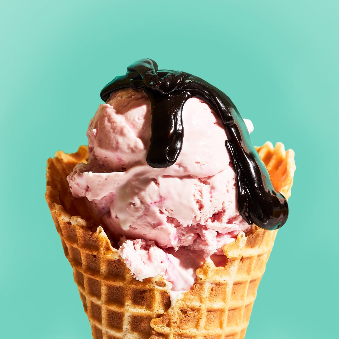 a scoop of pink ice cream in a waffle cone with a drizzle of chocolate syrup.