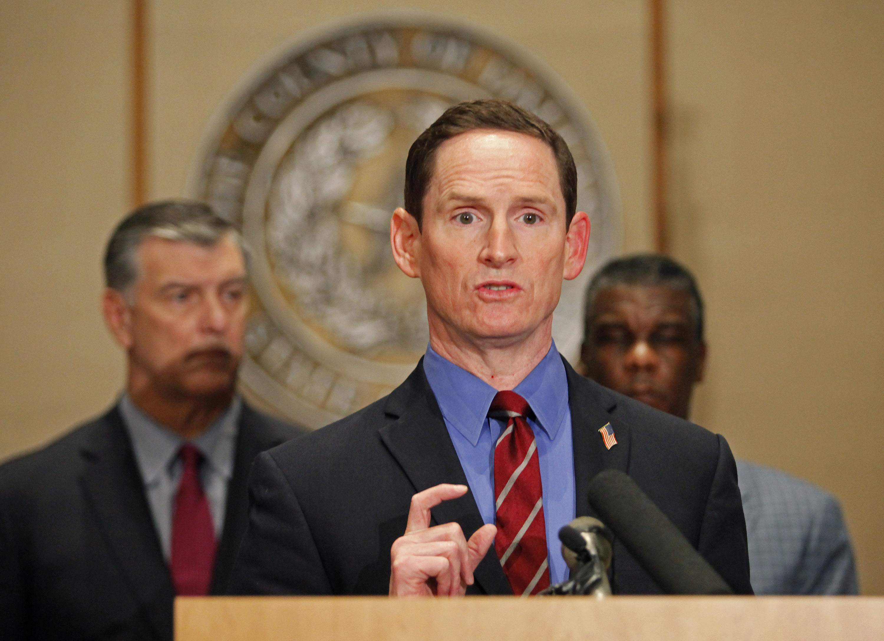 Dallas County judge Clay Jenkins, wearing a grey suit, blue shirt, and red tie, standing at a podium.
