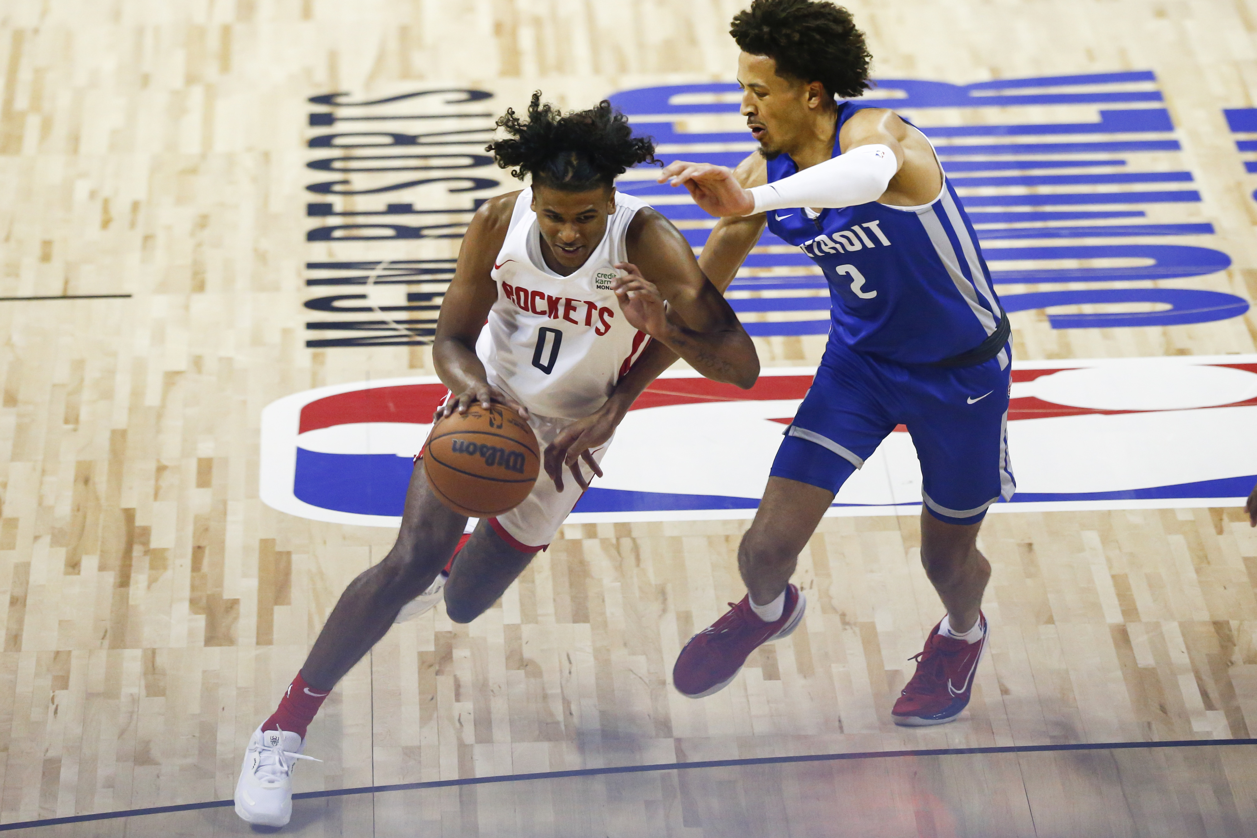 Houston Rockets' Jalen Green (0) drives to the basket under pressure from Detroit Pistons' Cade Cunningham (2).