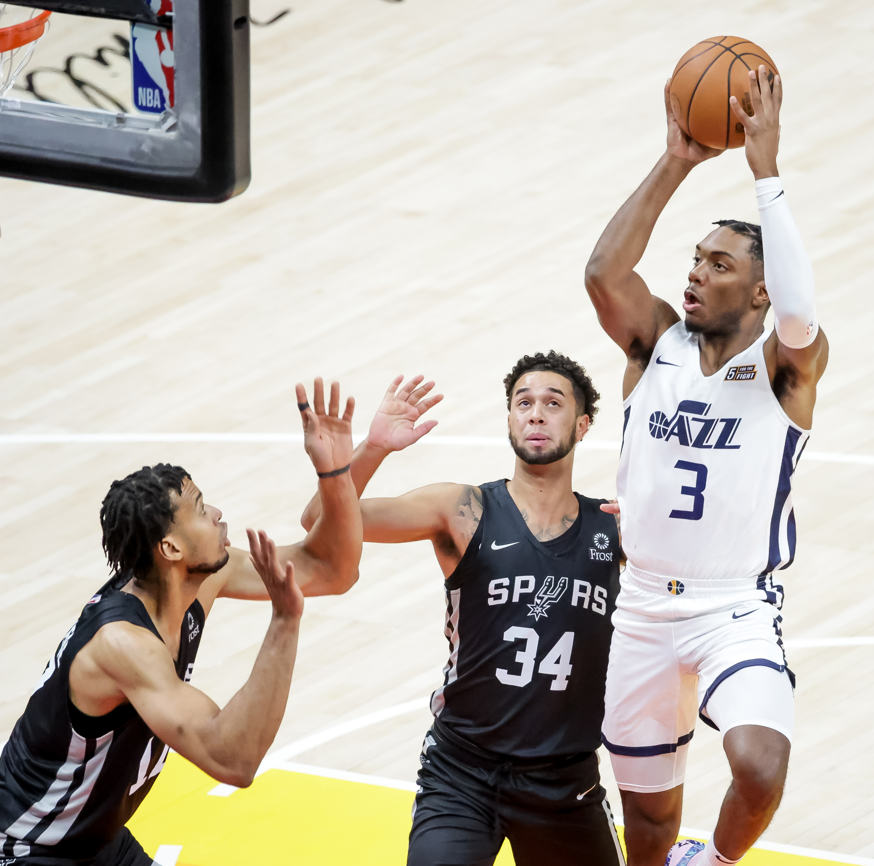 Utah Jazz guard Trent Forrest shoots over San Antonio's Skal Labissiere and Anthony Mathis during Summer League game at Vivint Arena in Salt Lake City on Tuesday, Aug. 3, 2021.