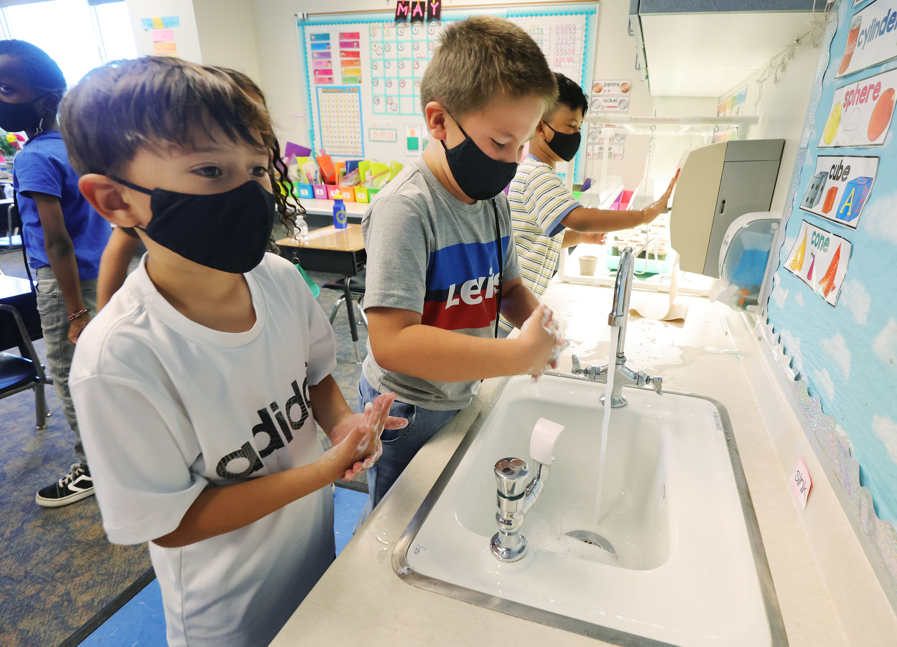 First graders Gilbert Grant and Monty Fox wear masks as they wash their hands at Woodrow Wilson Elementary in Salt Lake City.