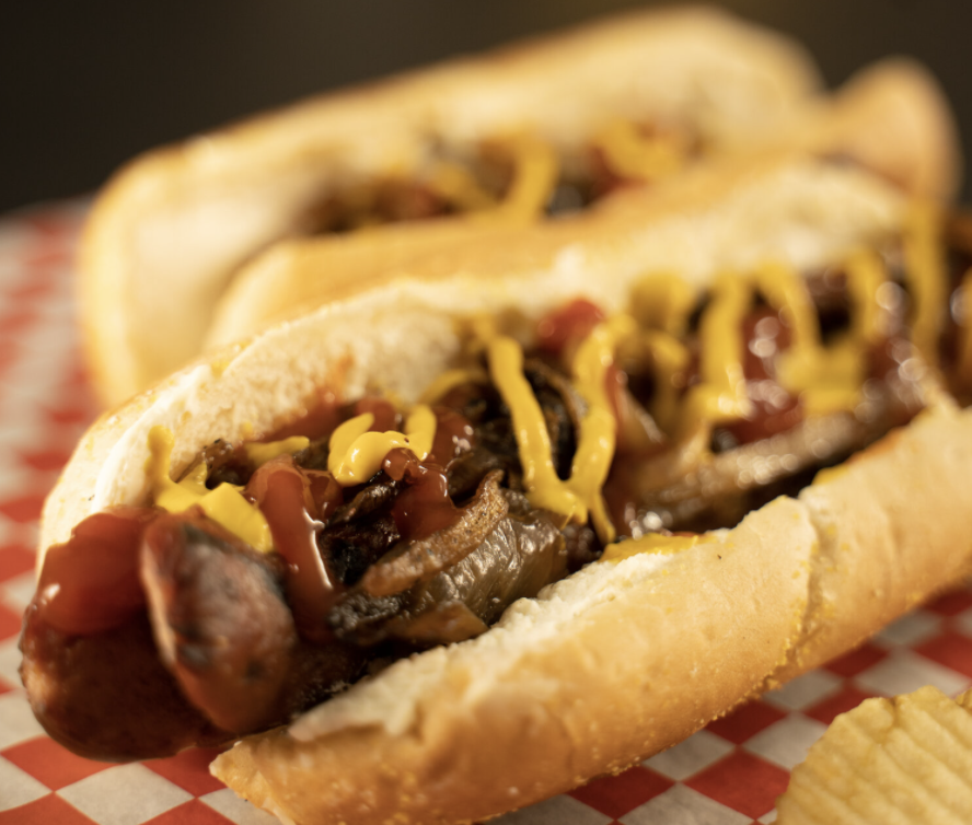 A closeup of a hot dog covered in ketchup, mustard, and grilled onions.
