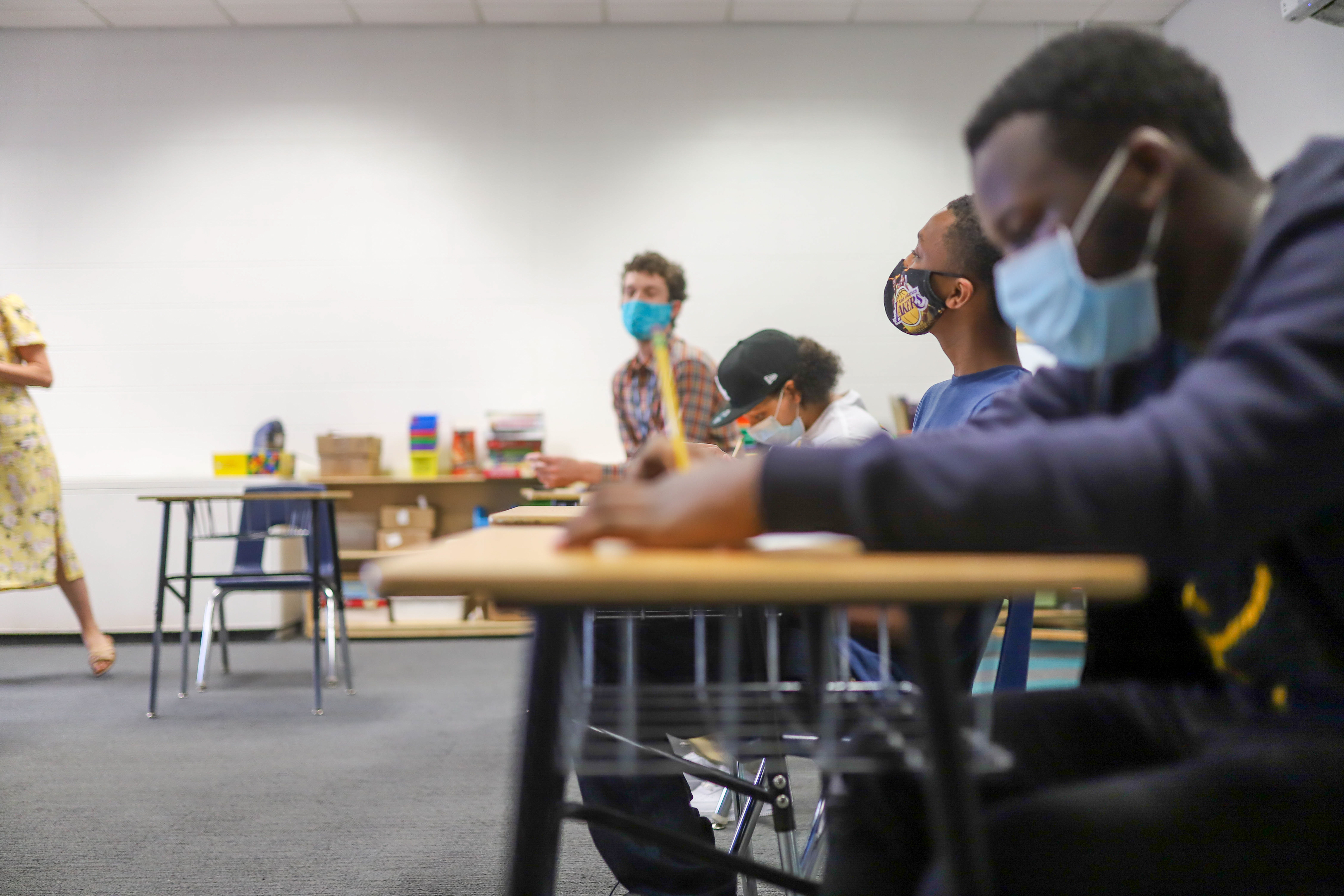 Four students wearing masks work at their desks in a classroom.