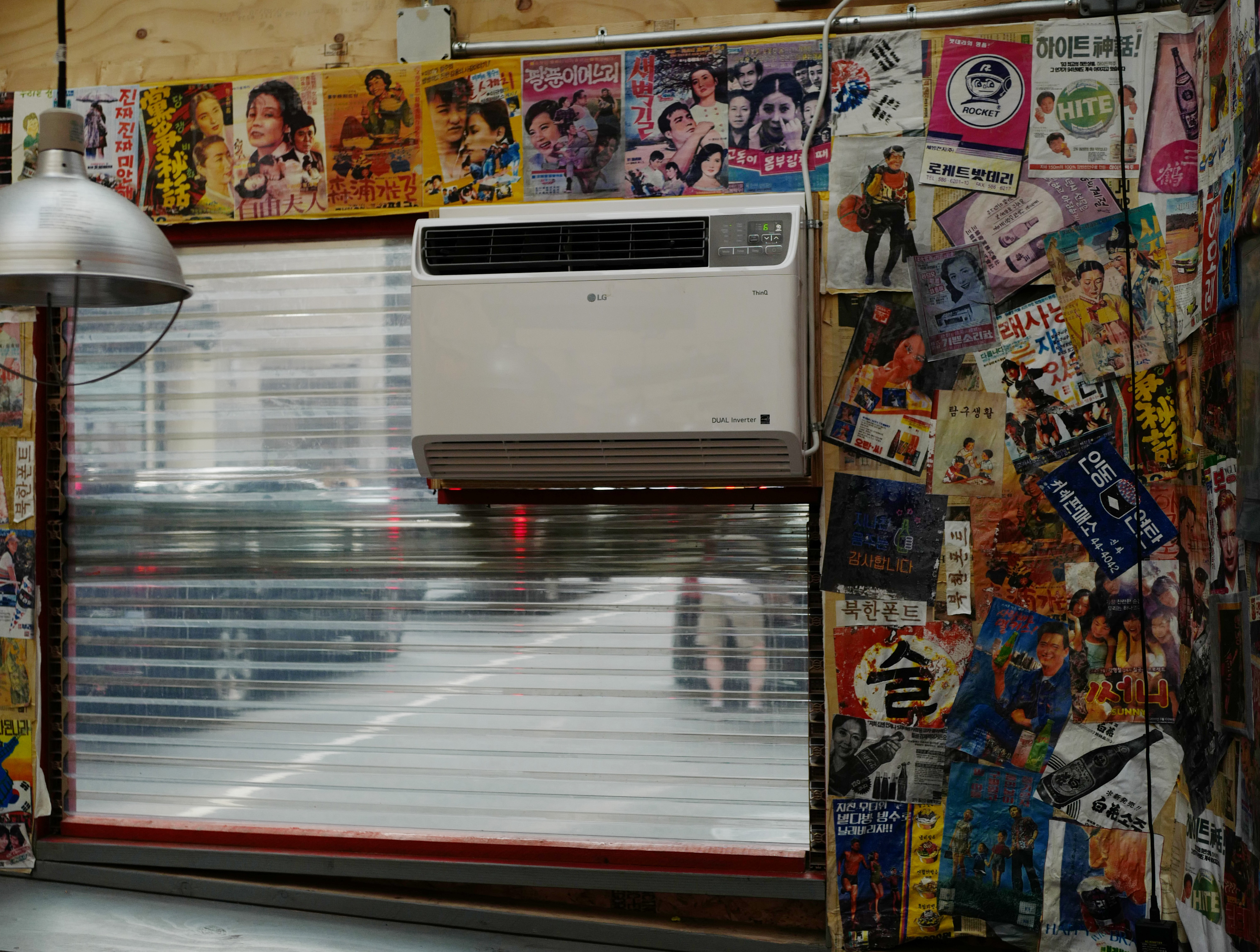 An air conditioning unit is installed in a plastic window. Vintage posters are pasted to the wall around it.