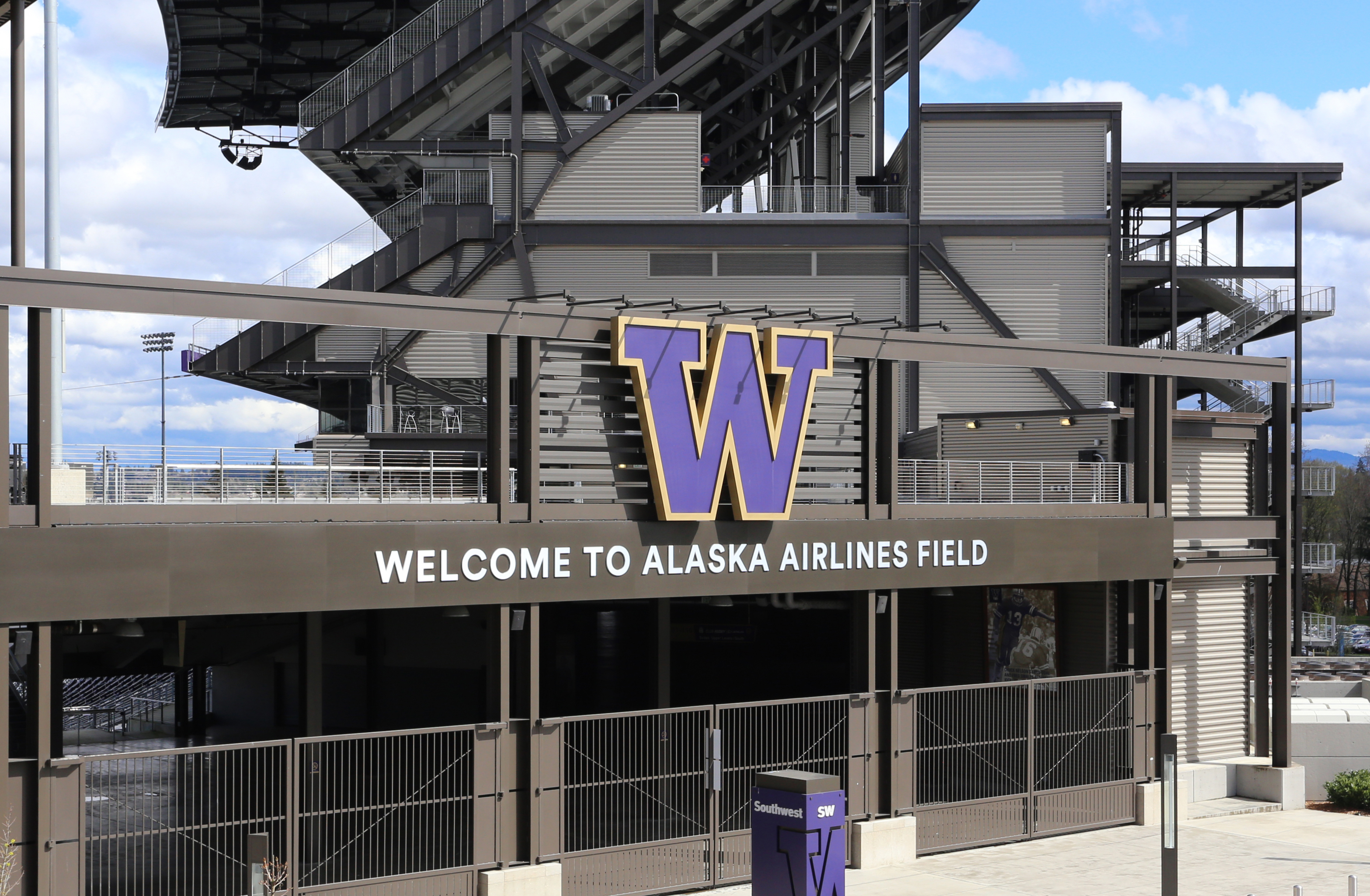 """The exterior of Husky Stadium, which has the school's purple """"W"""" logo out front along with a sign that says """"Welcome to Alaska Airlines Field"""""""