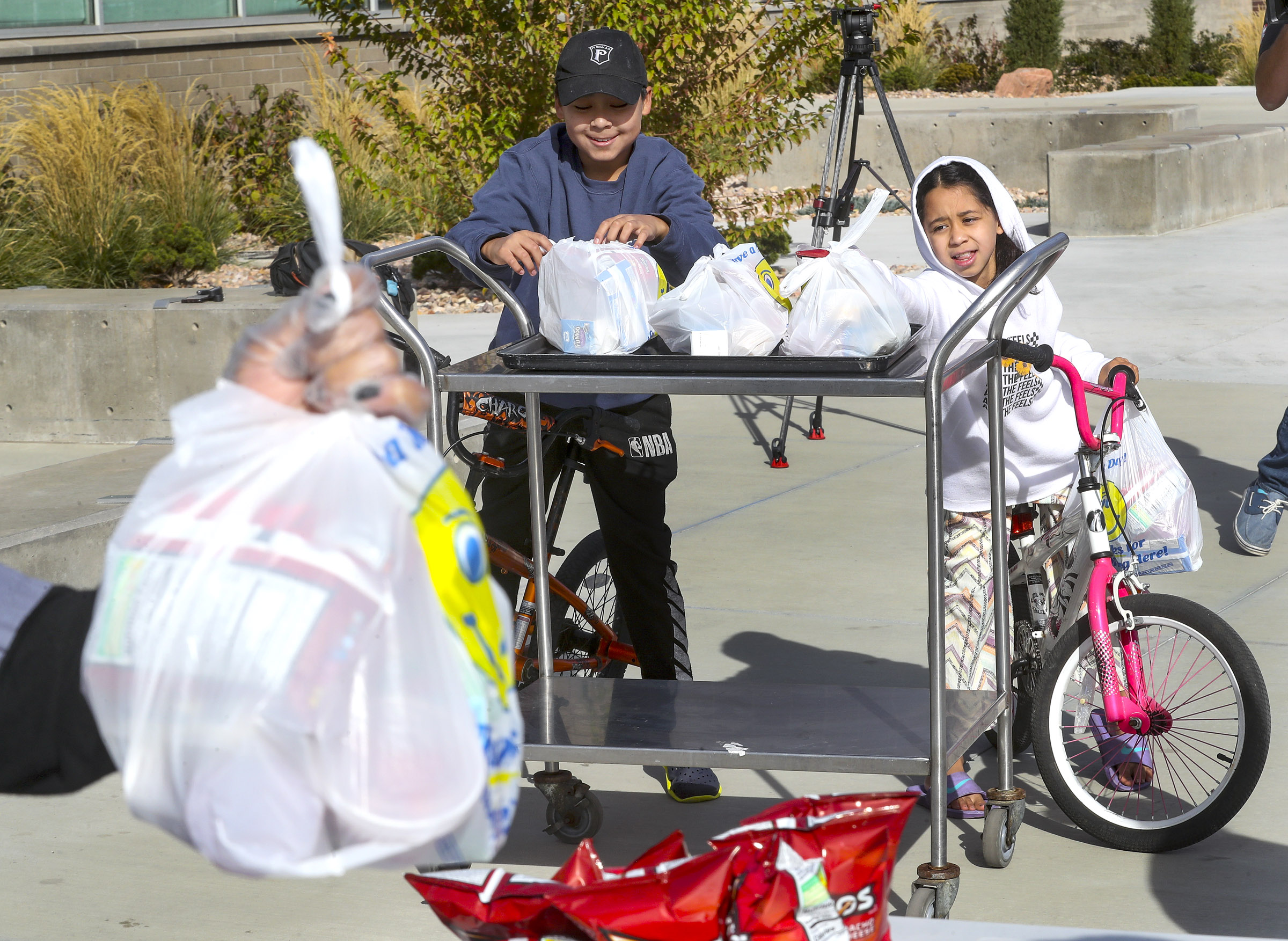 Jerson Arroyocruz and his sister Genesis get grab-and-go lunches for their family at Edison Elementary School. Expanded child nutrition help is part of the $3.5 trillion budget proposal Democrats hope to get through reconciliation,