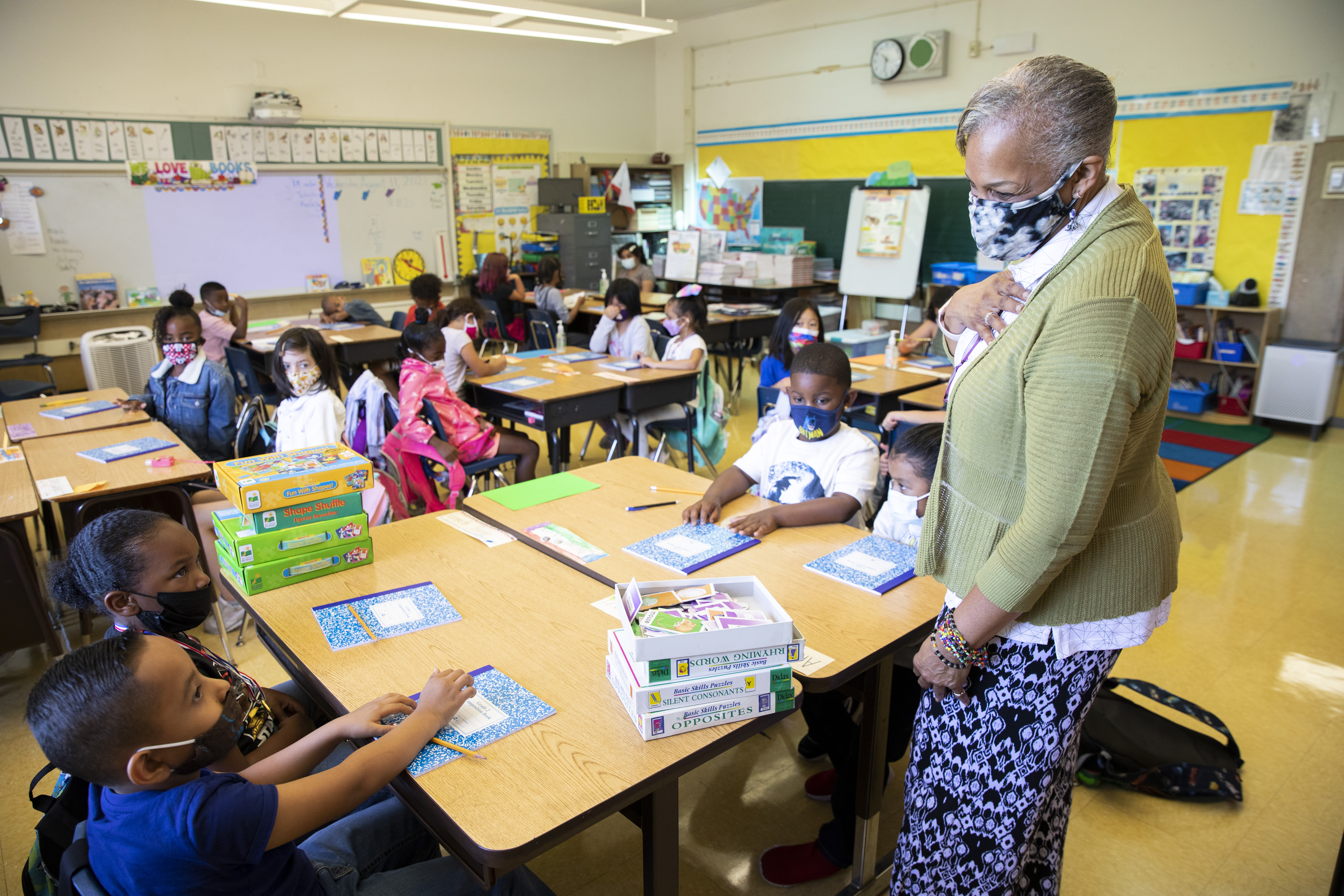 An older female elementary teacher gestures at a table of young students in her full classroom, all of them wearing masks due to COVID protocols.