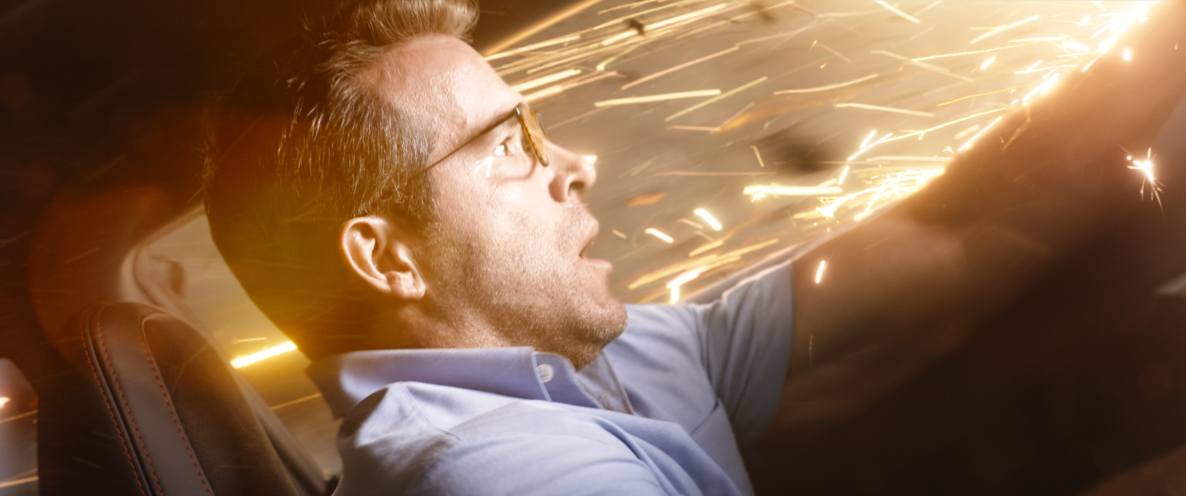 Ryan Reynolds in a blue shirt and glasses in a vehicle, while sparks fly around him.