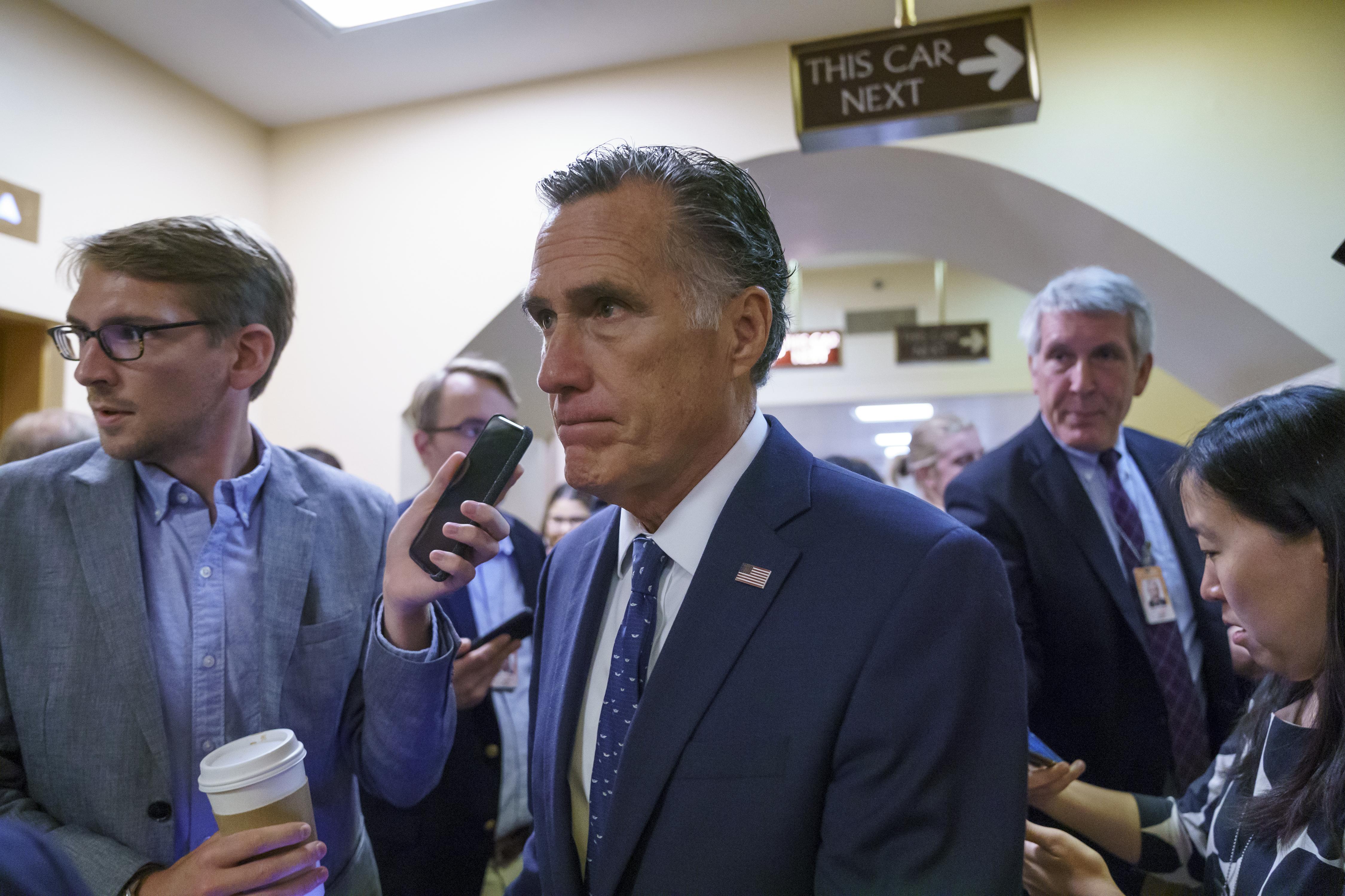 Utah Senator Mitt Romney talks to reporters at the Capitol in Washington.