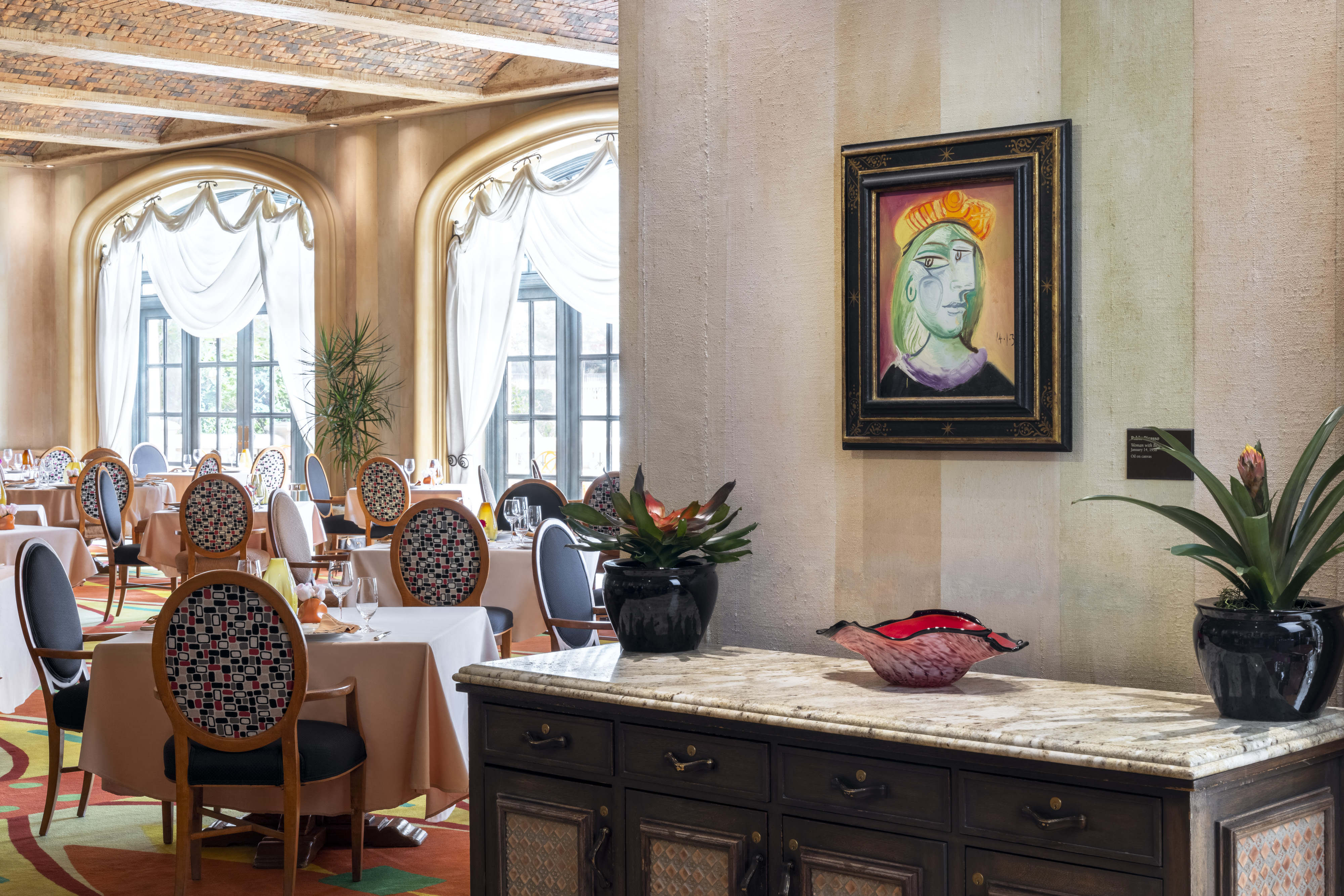 A cubist painting hangs over a sideboard in a restaurant