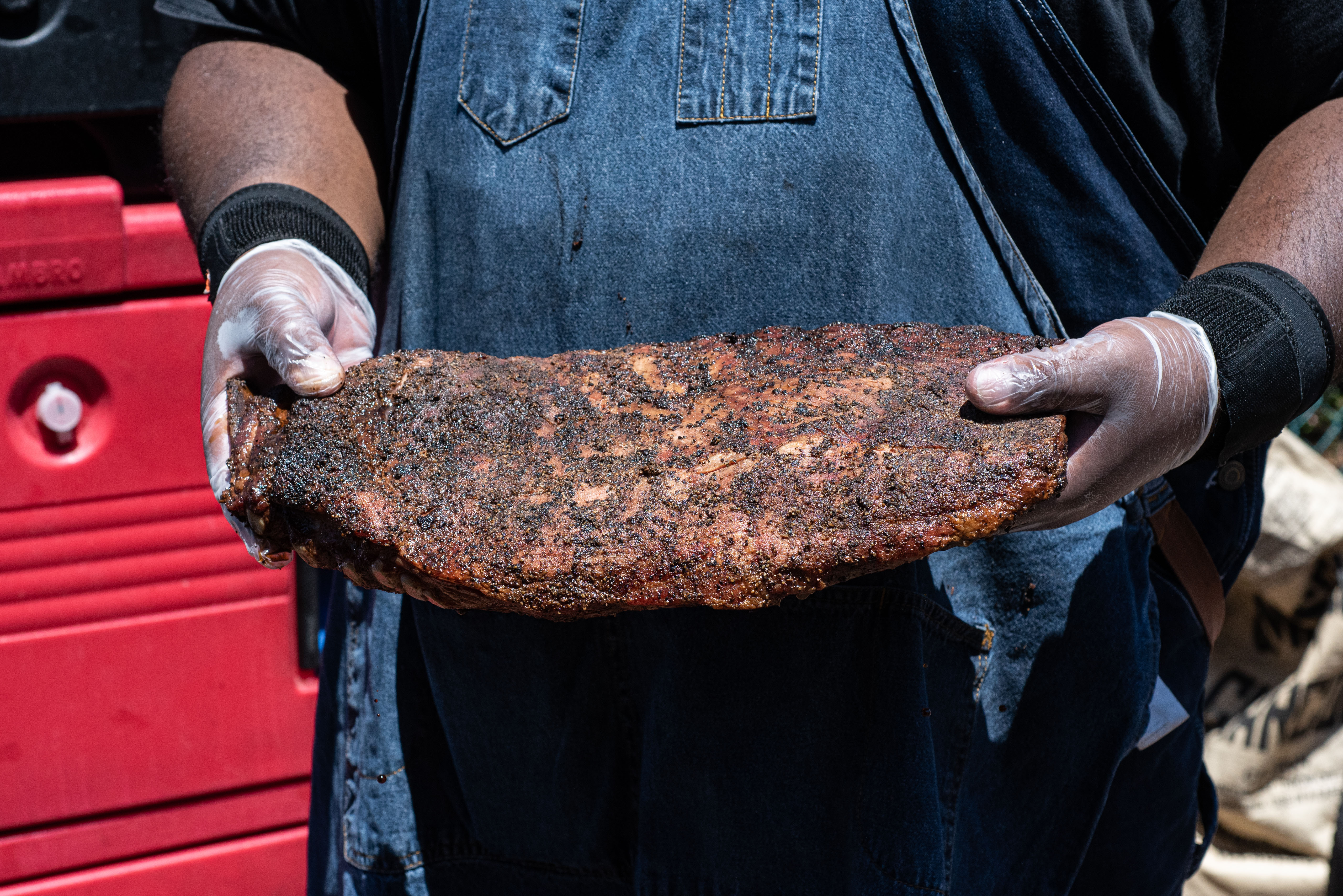A man in denim overall holds an uncut full rack of ribs in front of him.