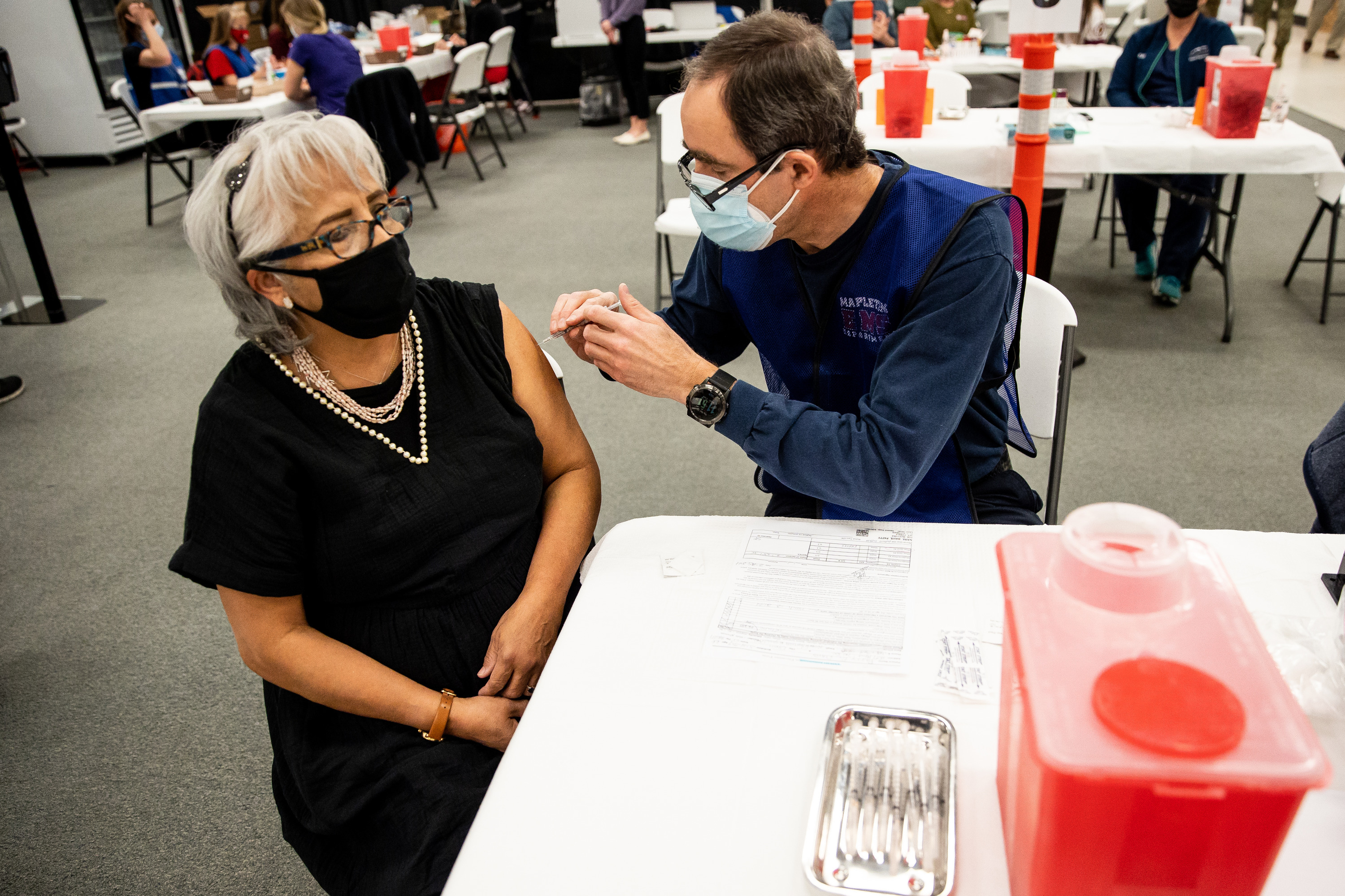 An EMT delivers a COVID-19 vaccination to a woman in Spanish Fork.