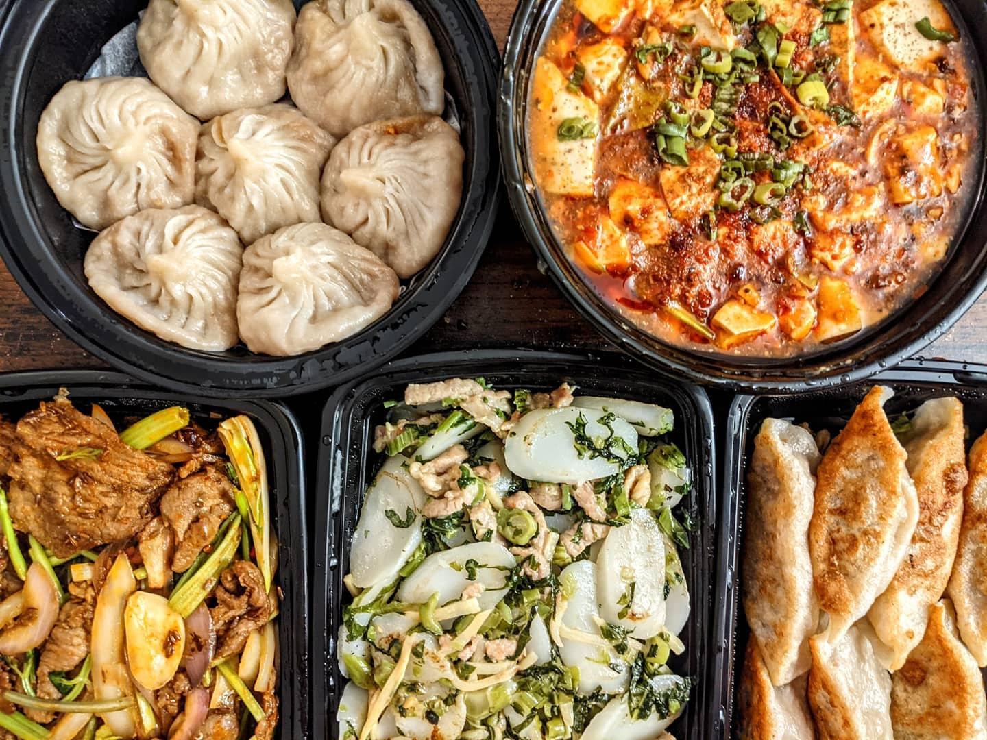Overhead view of two round and three rectangular black plastic takeout containers of Chinese food, including two kinds of dumplings, ma po tofu, oval rice cakes with greens and slivers of pork, and more.