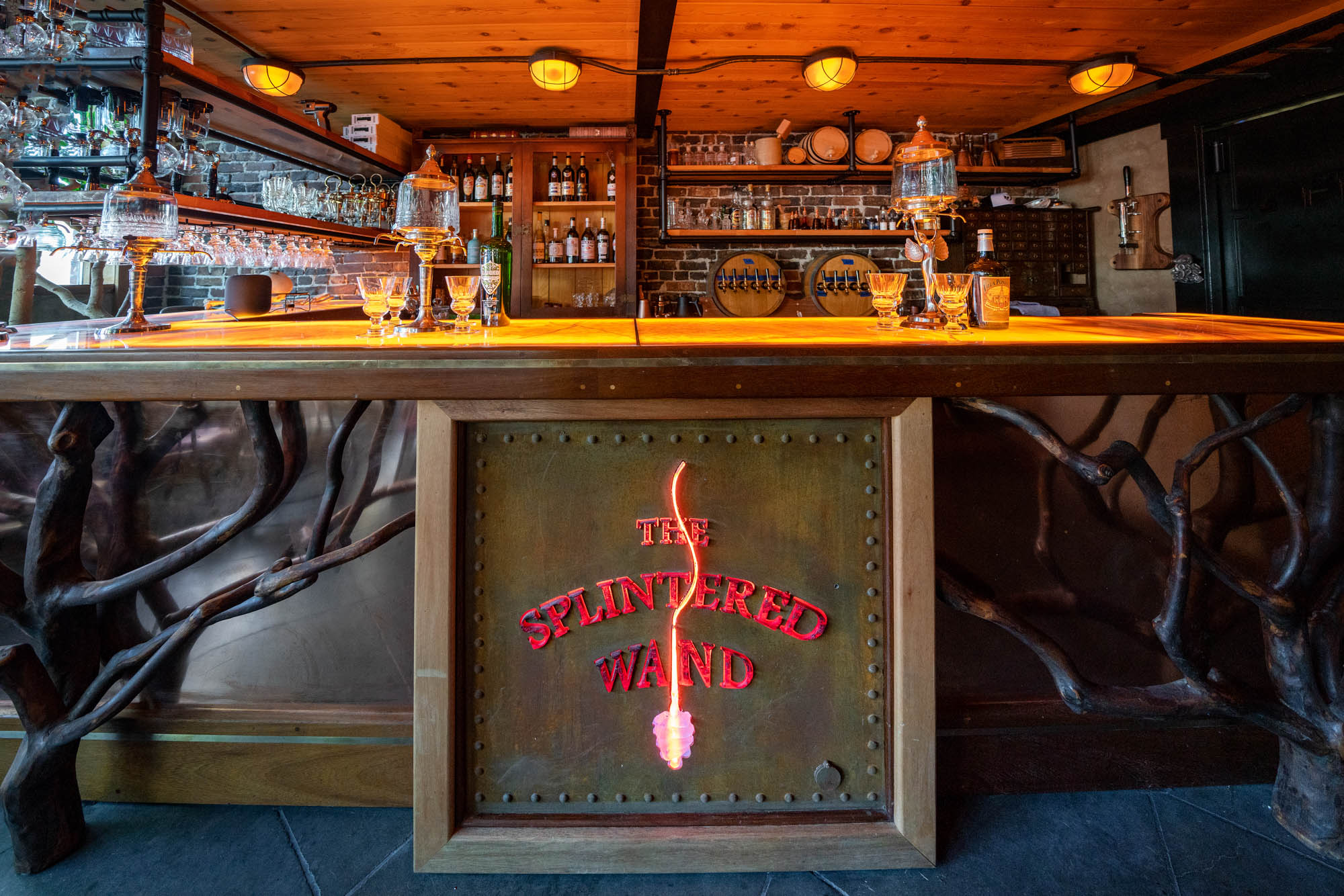 """A bar lit with soft orange overhead lamps, decorated with a sign that says """"The Splintered Wand"""" in glowing red letters and branches of a plant snaking below."""