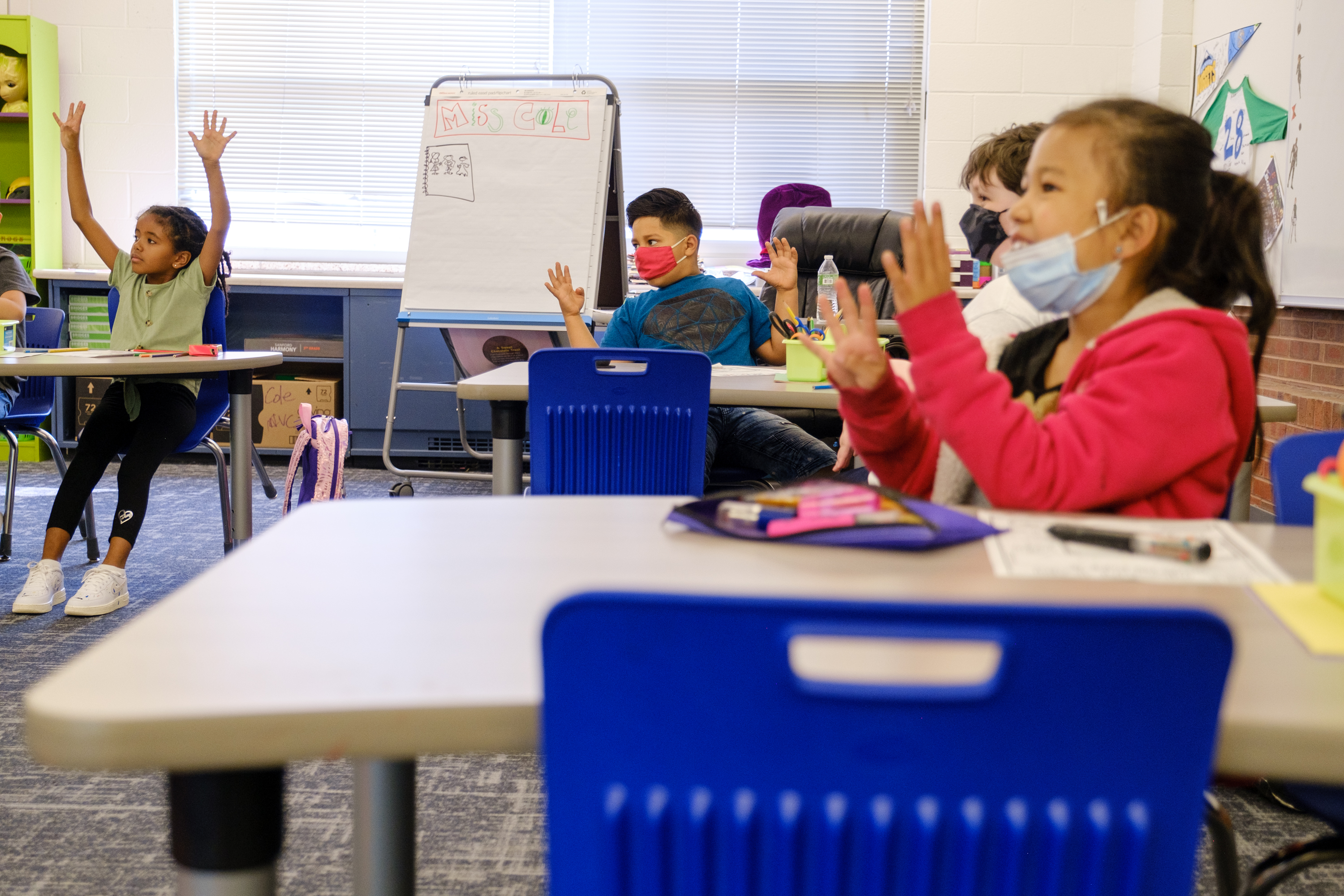 Elementary students excitedly raise their hands together at their desks. Some students are wearing protective masks, while others are not.