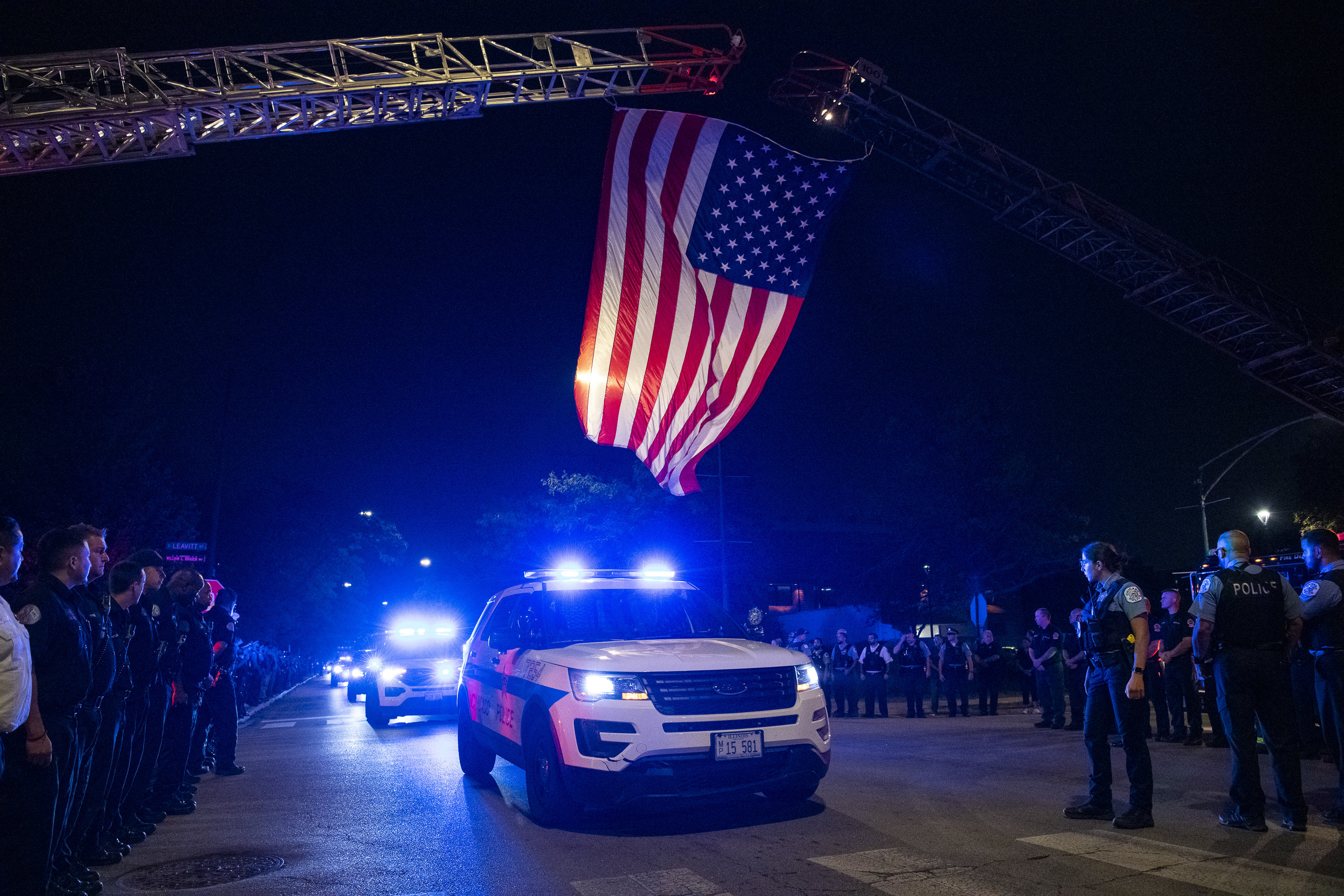 A Chicago police procession drives by the Cook County Medical Examiner's Office early Sunday morning, Aug. 8, 2021. The procession was in honor of Officer Ella French, who was shot and killed during a traffic stop in West Englewood Saturday night.