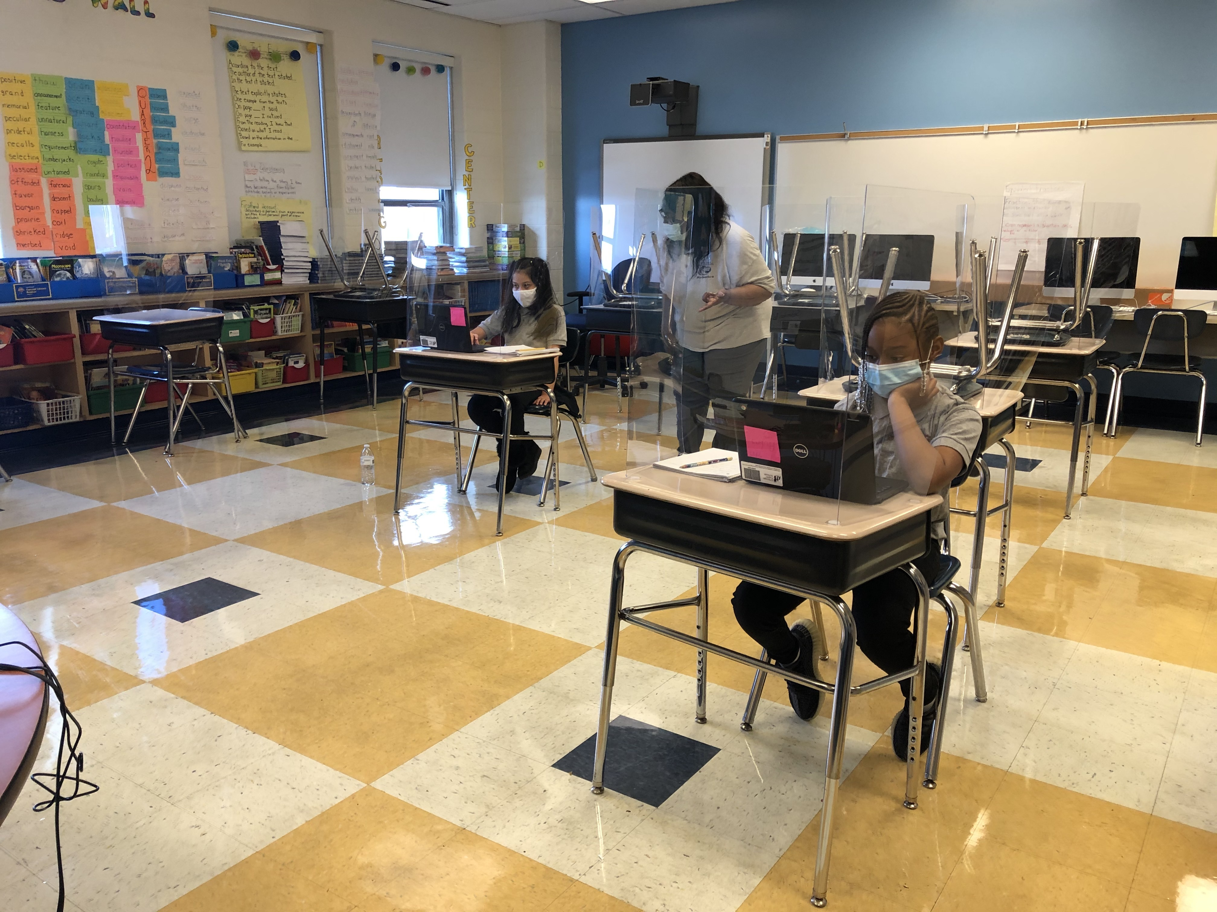 Students wearing face masks sit at desks behind plastic shields in a Chicago classroom with a yellow, cream, and black checkerboard floor and a blue wall. They are working on laptop computers as a teacher wearing a white top watches.
