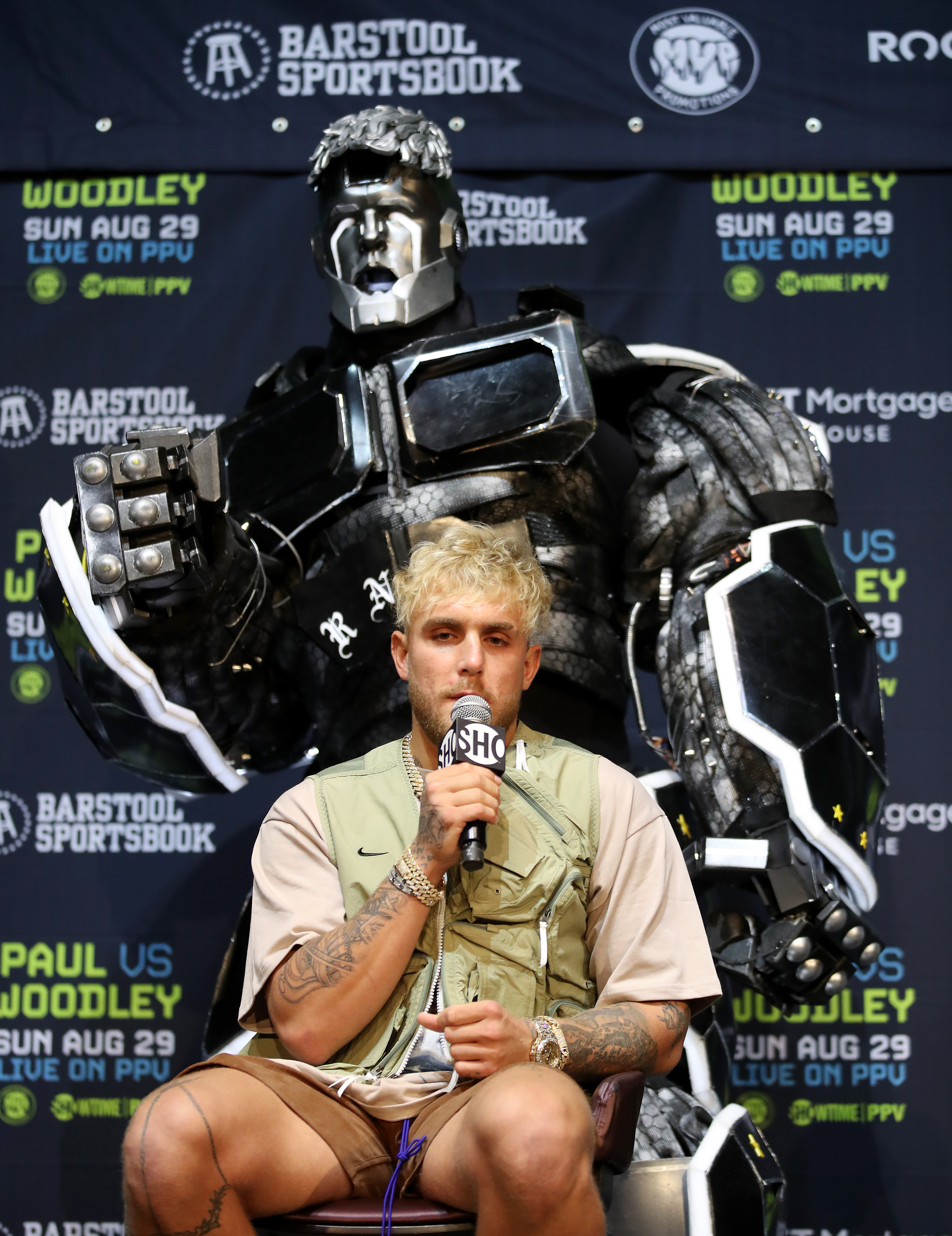 Jake Paul takes questions in front of a giant robot during a press conference for his boxing match with Tyron Woodley.