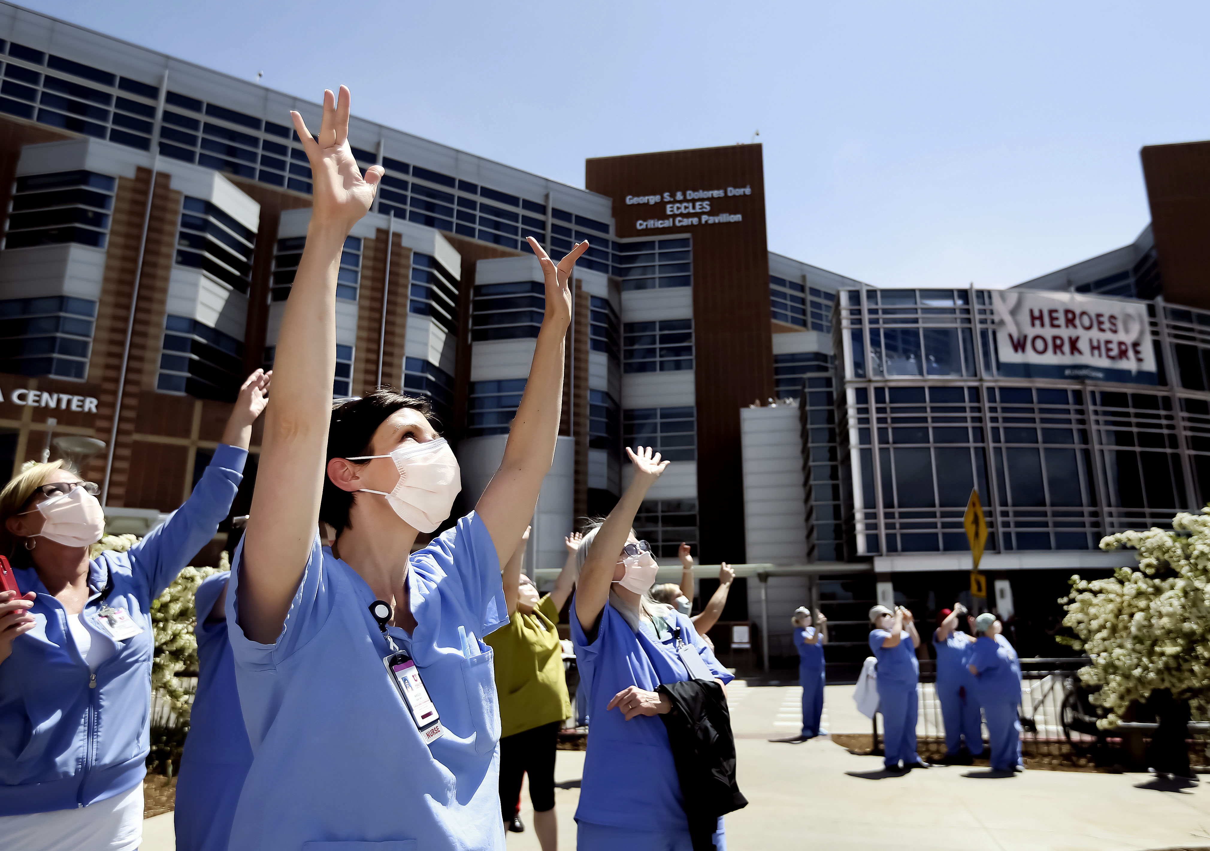 University of Utah Hospital nurse Nikole Ihler waves as Hill Air Force Base's 388th Fighter Wing fly over the hospital.