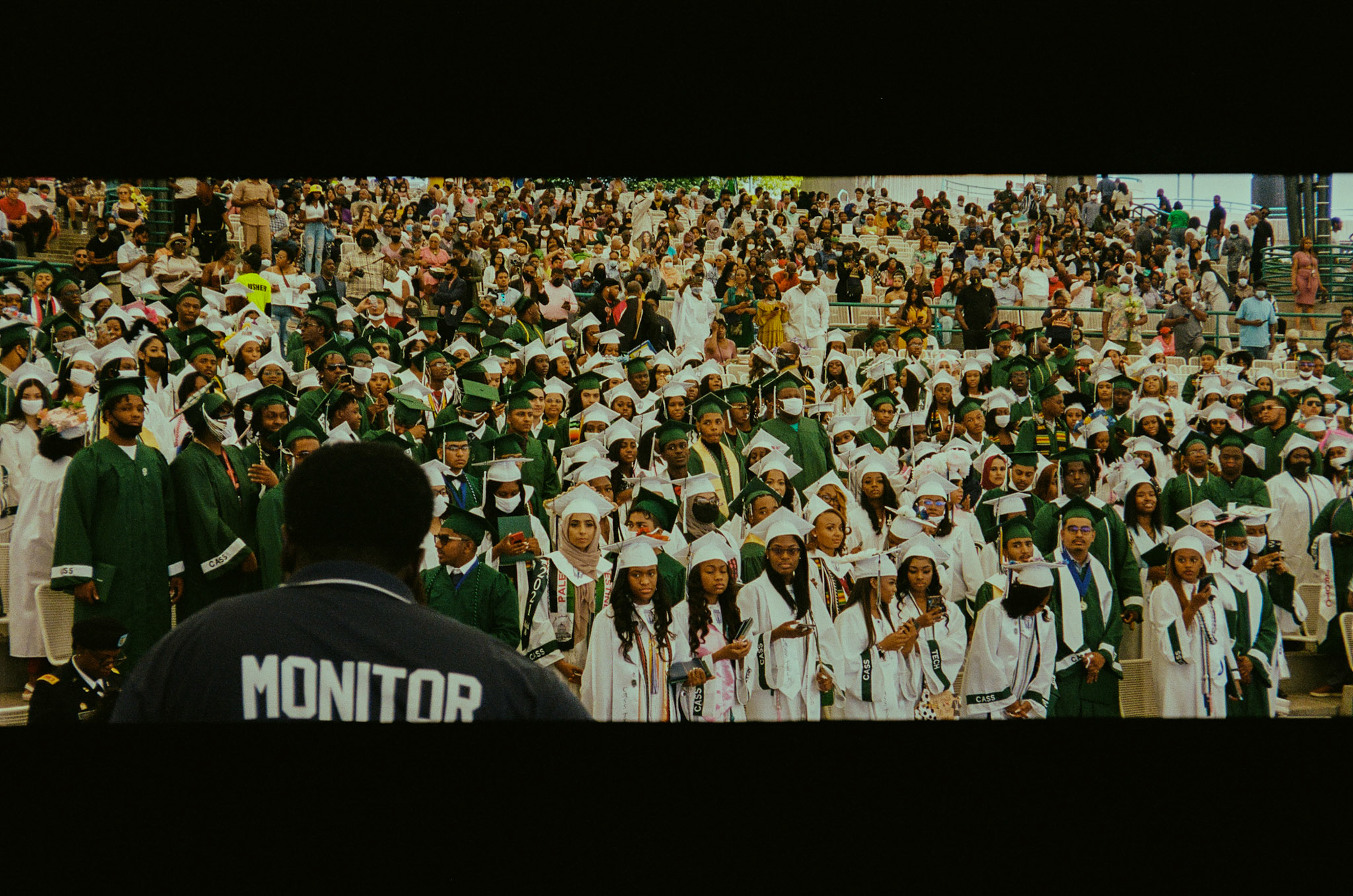 A large group of graduating high school students, wearing green and white caps and gowns, stand in neat rows as their parents look on behind them.