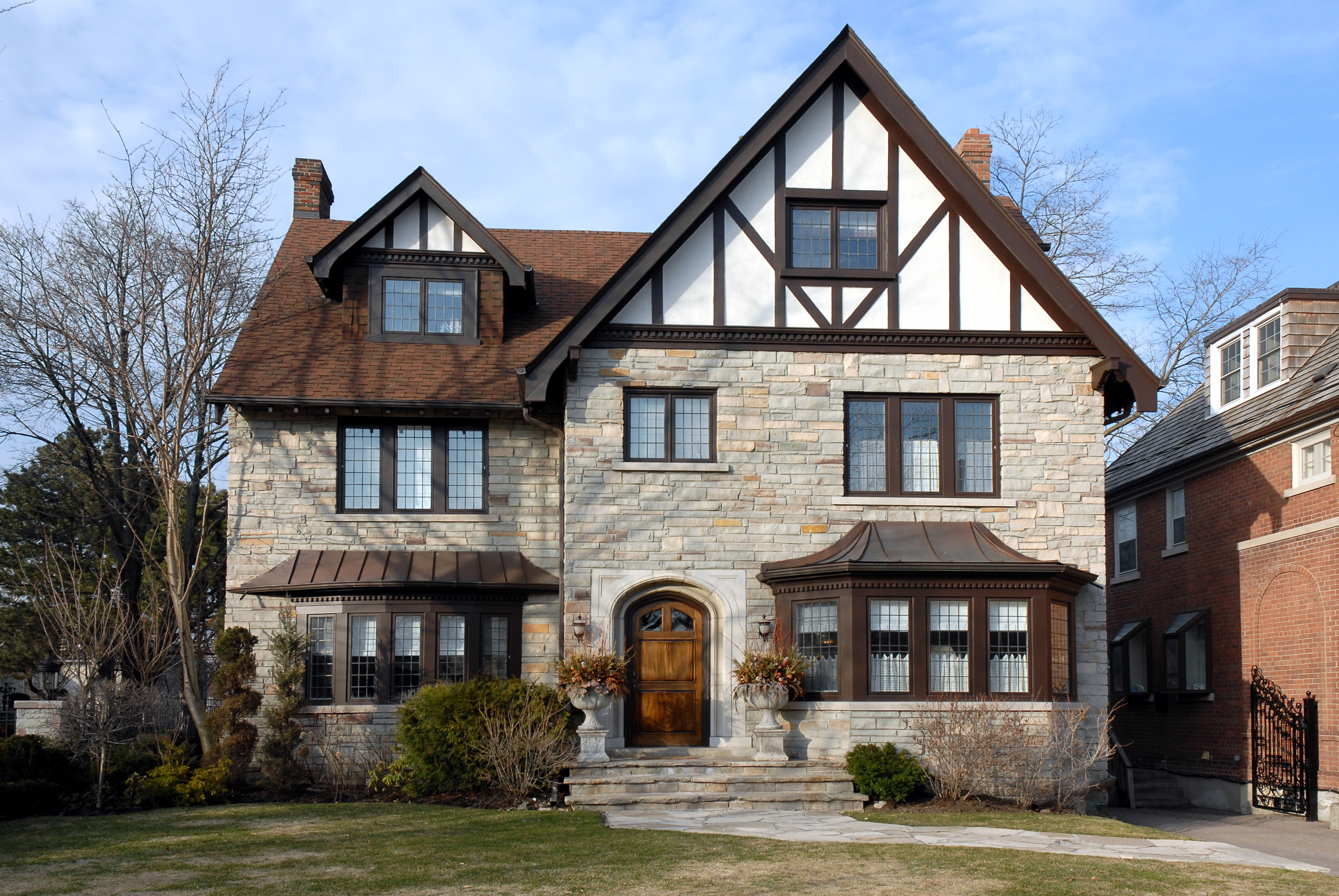 A Tudor style house in a downtown area with stone detailing and large front yard.