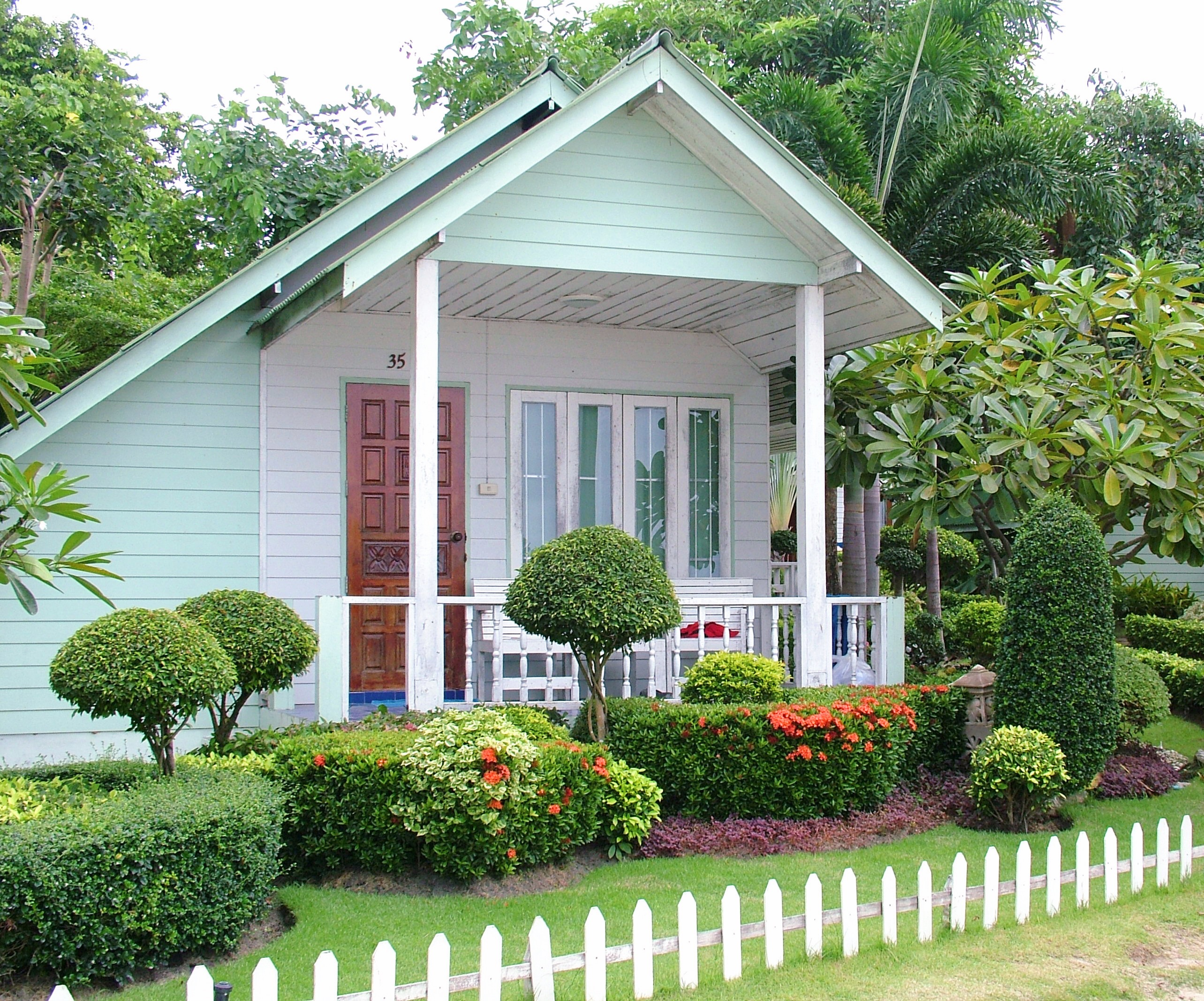A bungalow style house in a tropical area painted mint green with shrubs and small trees.