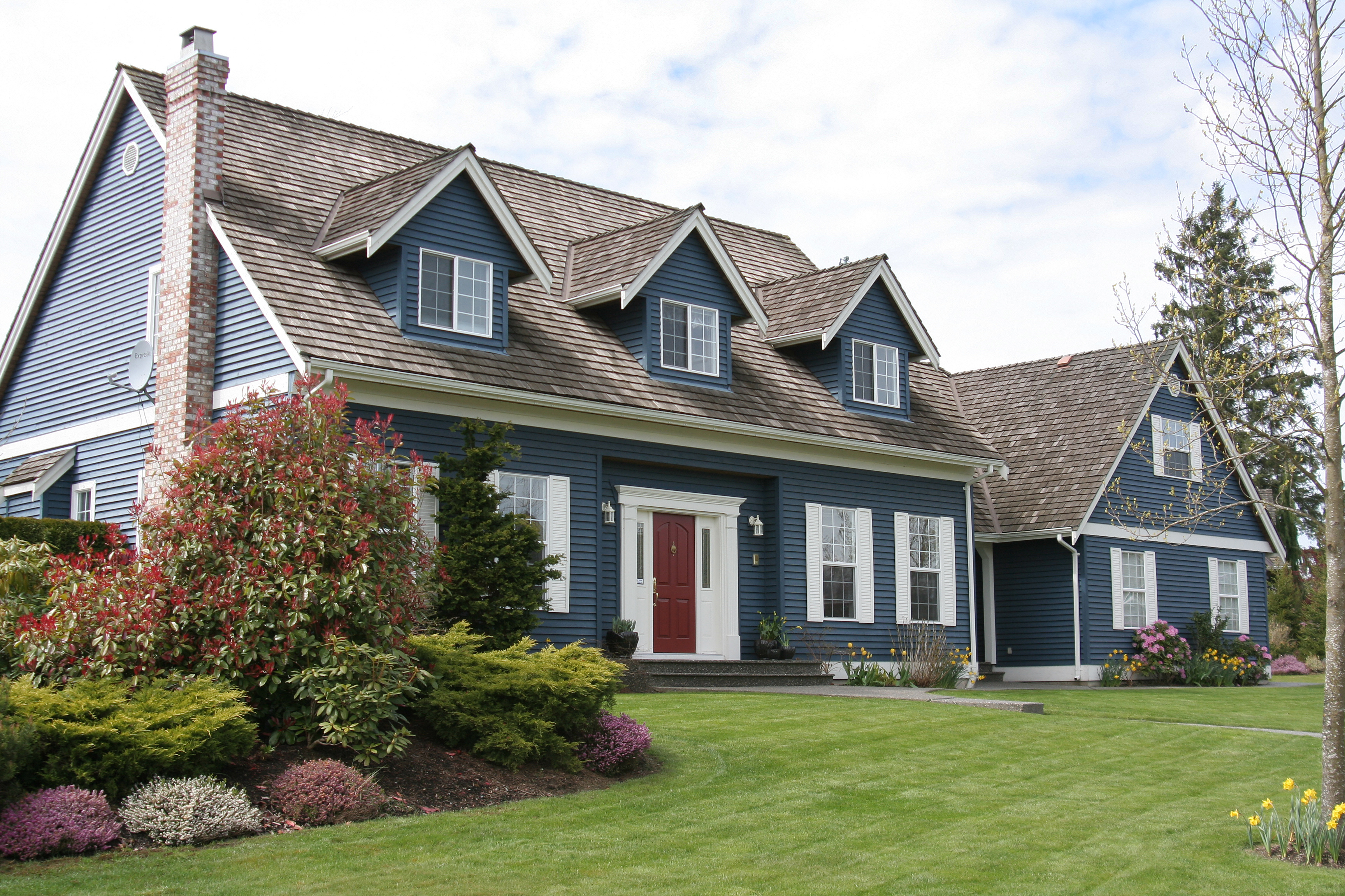 A navy blue home with large green yard and red front door.