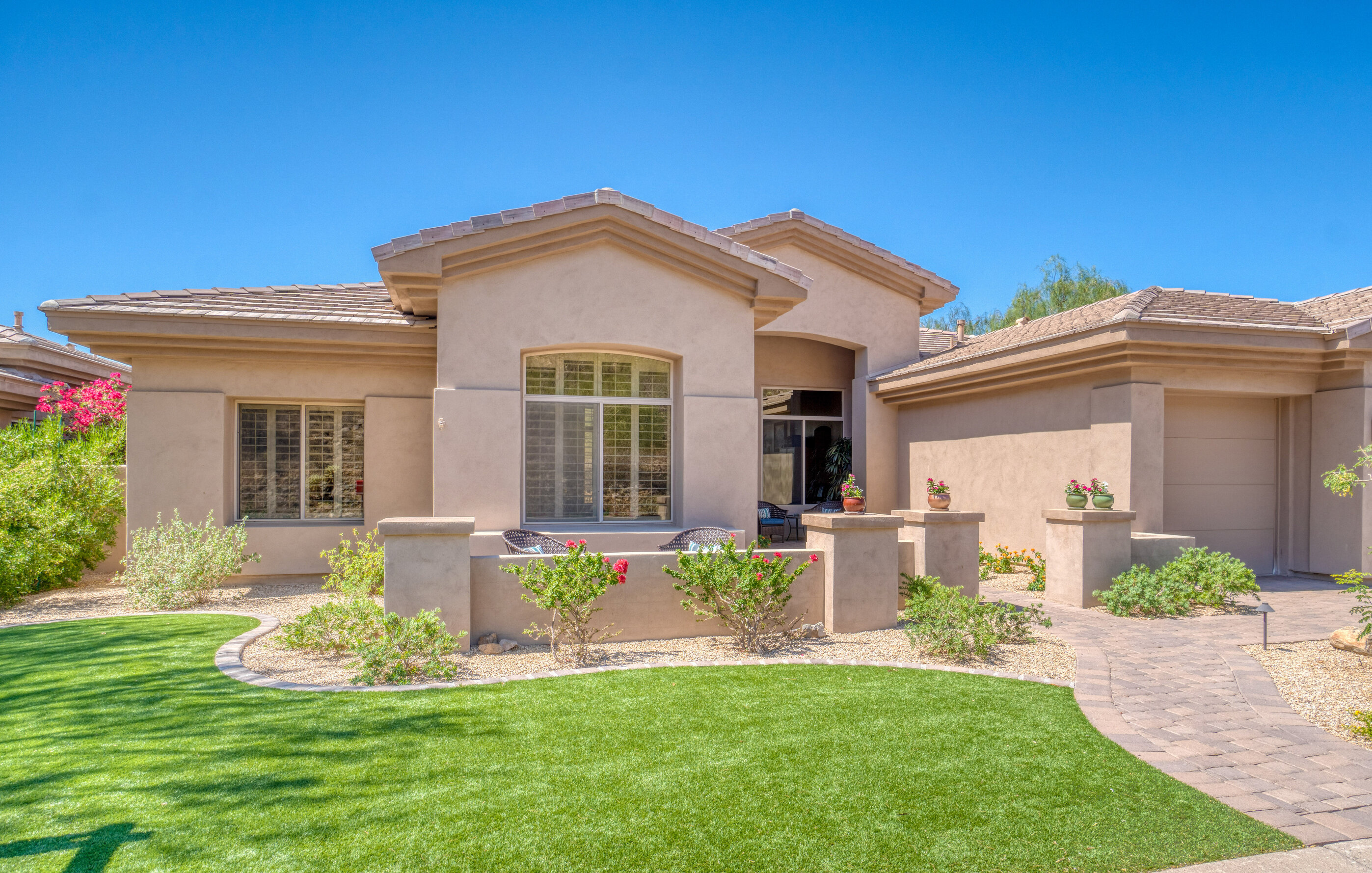 An Arizona home with green front yard and several green shrubs.