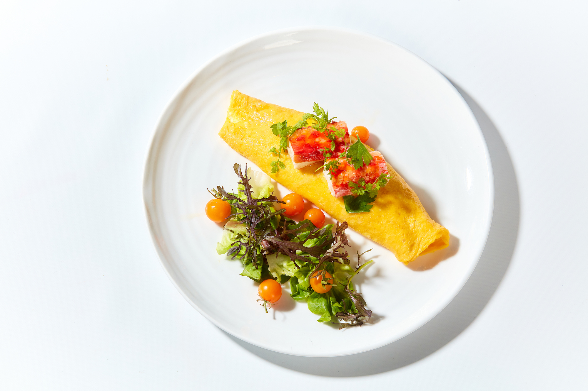 An omelet with a salad on a white plate