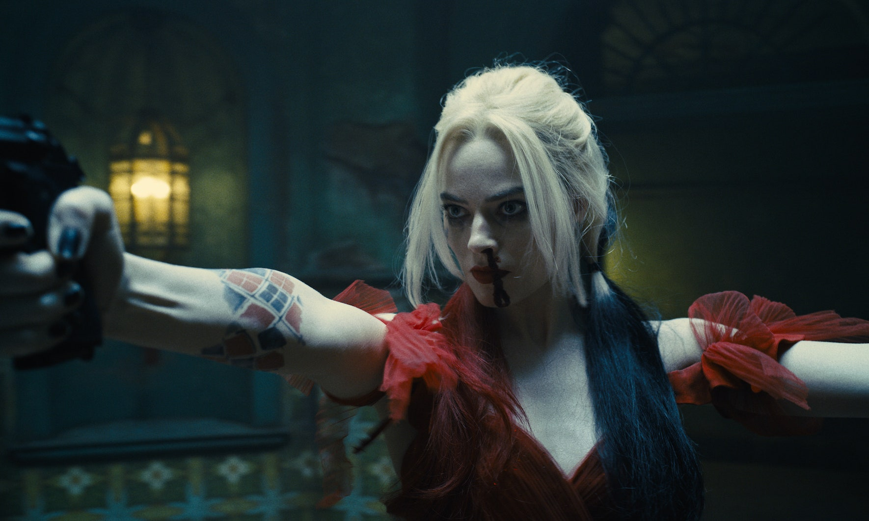 Harley Quinn points a gun at someone, blood dripping down her face. She's wearing a lovely ballgown.